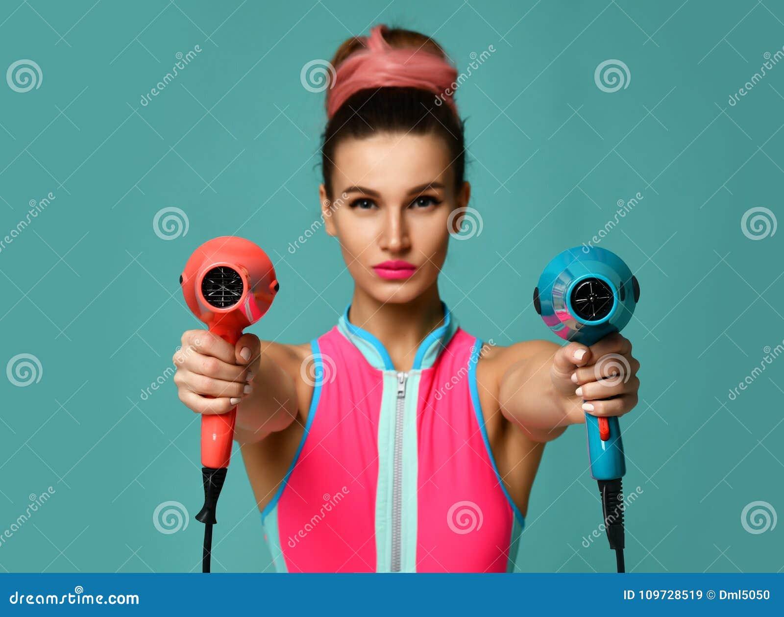 有吹风器的愉快的年轻深色的妇女在蓝色薄荷的背景