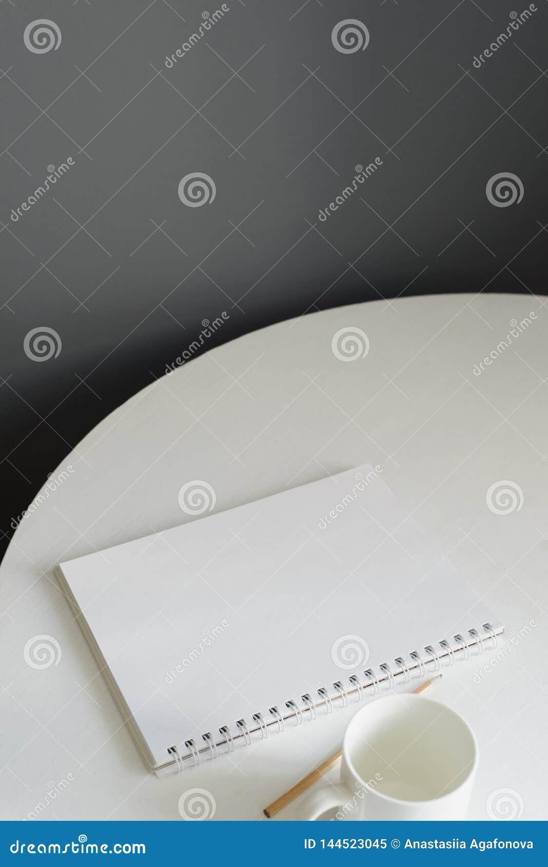 有咖啡杯和铅笔的空白的笔记本在白色木桌上