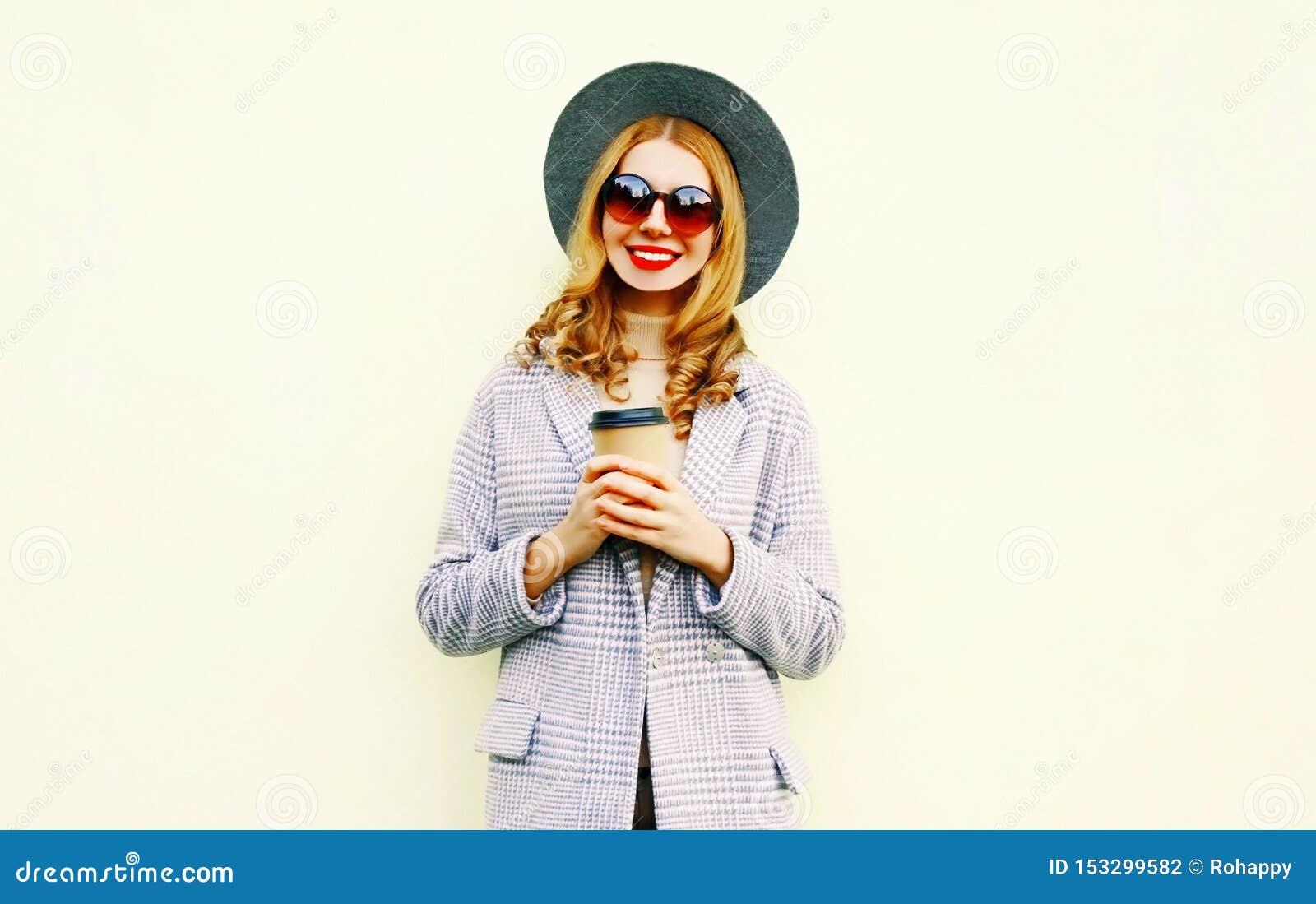 有咖啡杯的画象愉快的微笑的妇女在桃红色外套,在背景的圆的帽子