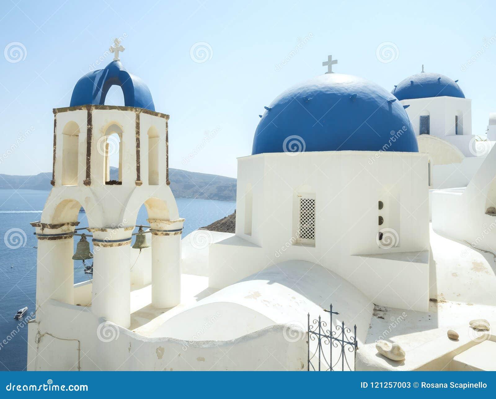 有响铃的白色教会和蓝色圆顶在Oia,圣托里尼,希腊海岛