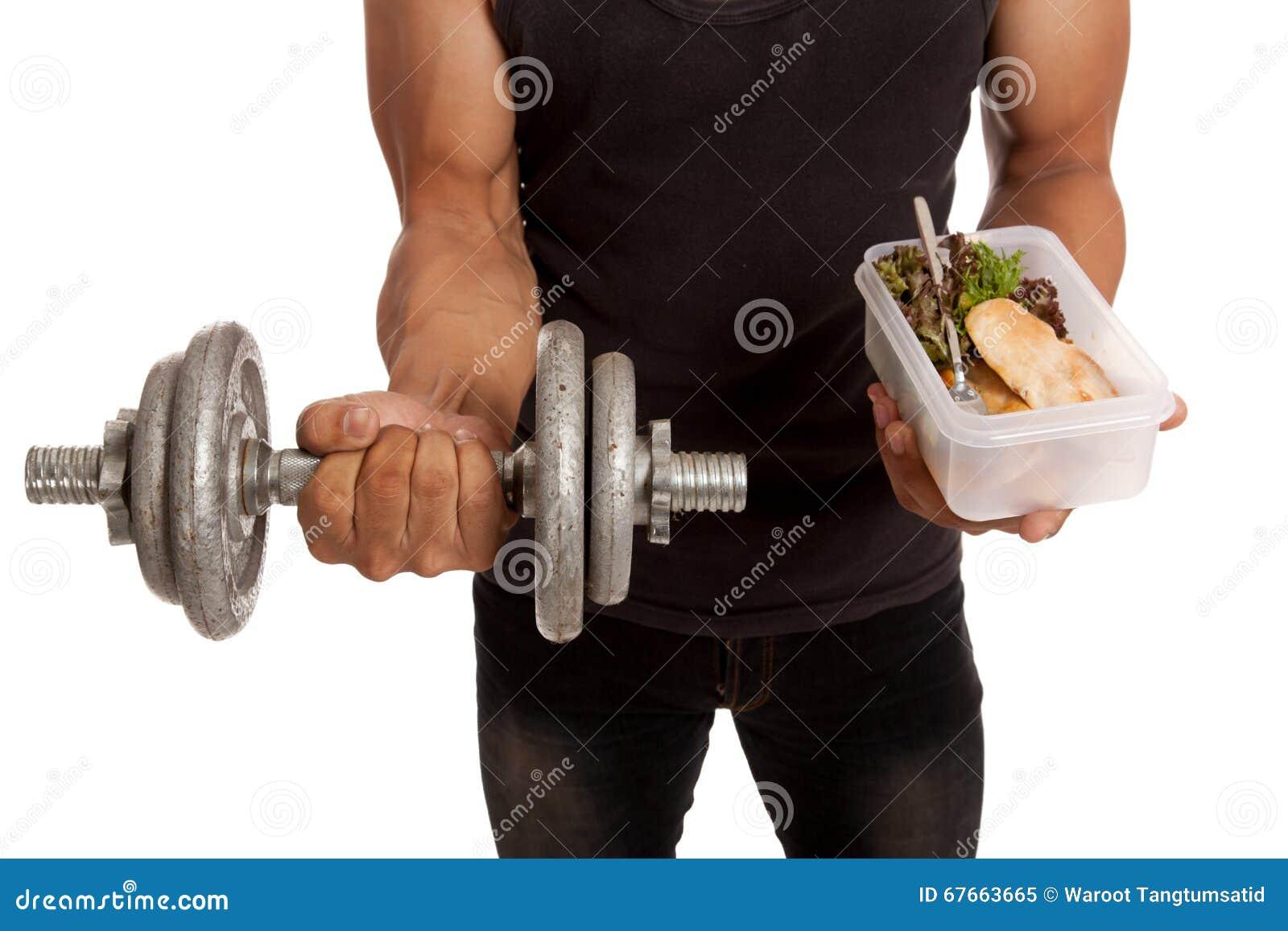 有哑铃的肌肉亚裔人和在箱子的干净的食物