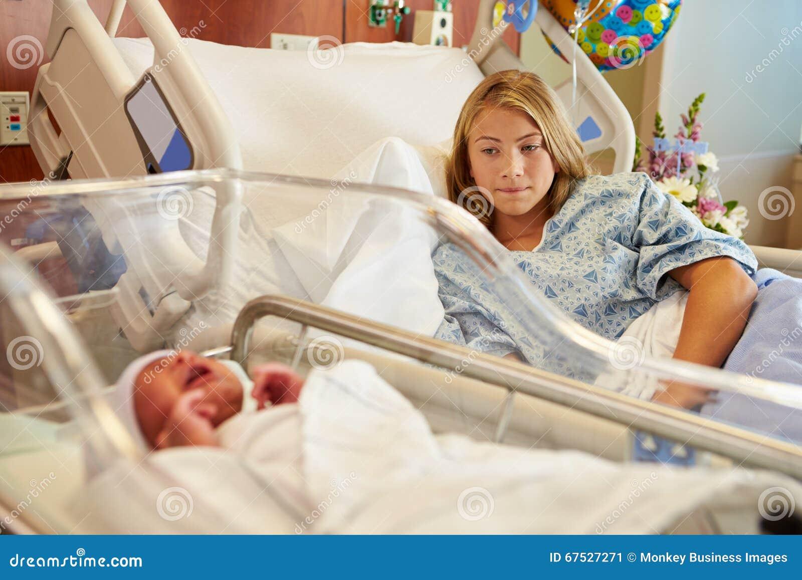 有哭泣的新出生的婴孩的担心的十几岁的女孩在医院