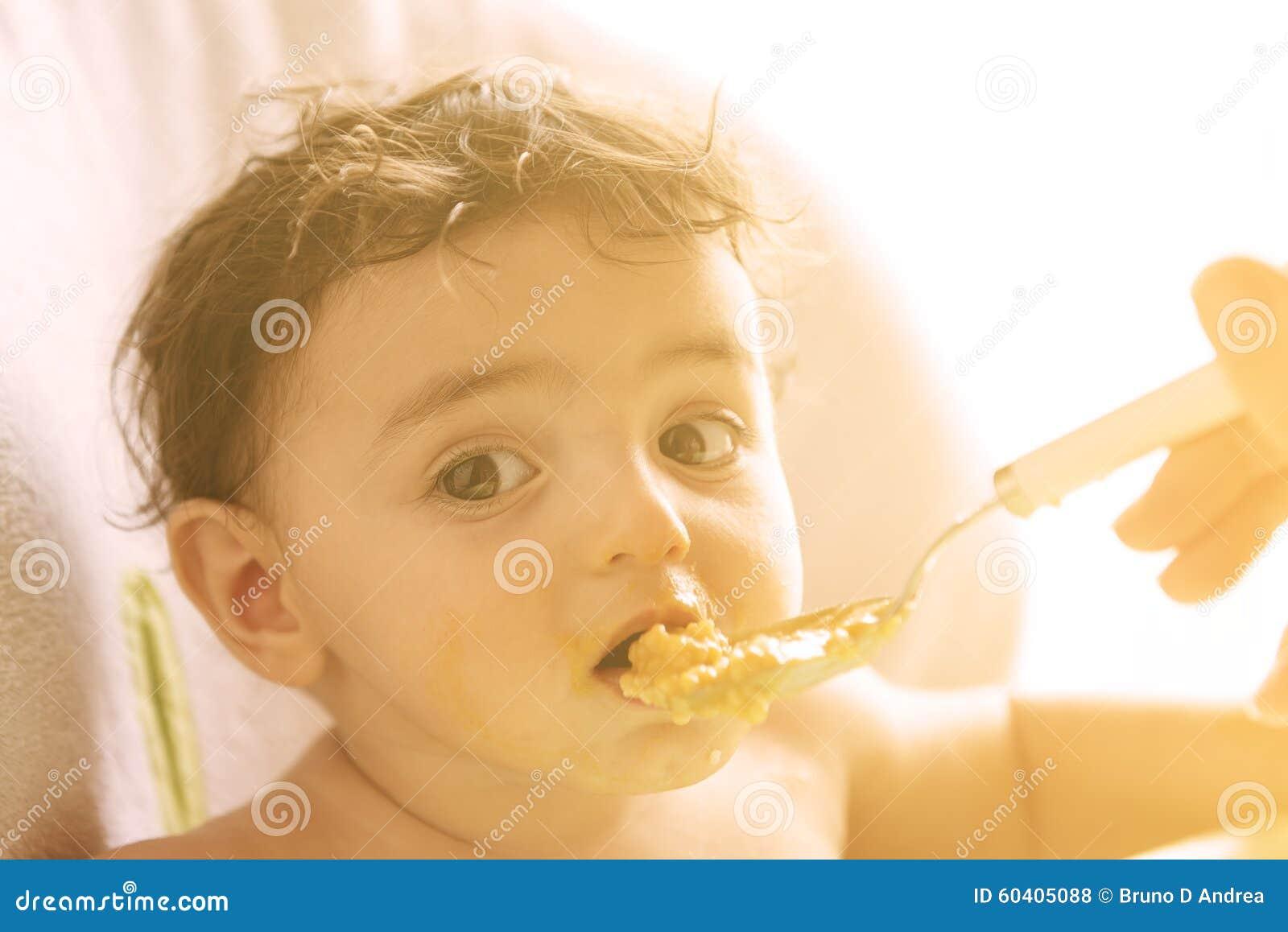 有哺养美好的逗人喜爱的小的s的匙子和粥的年轻母亲