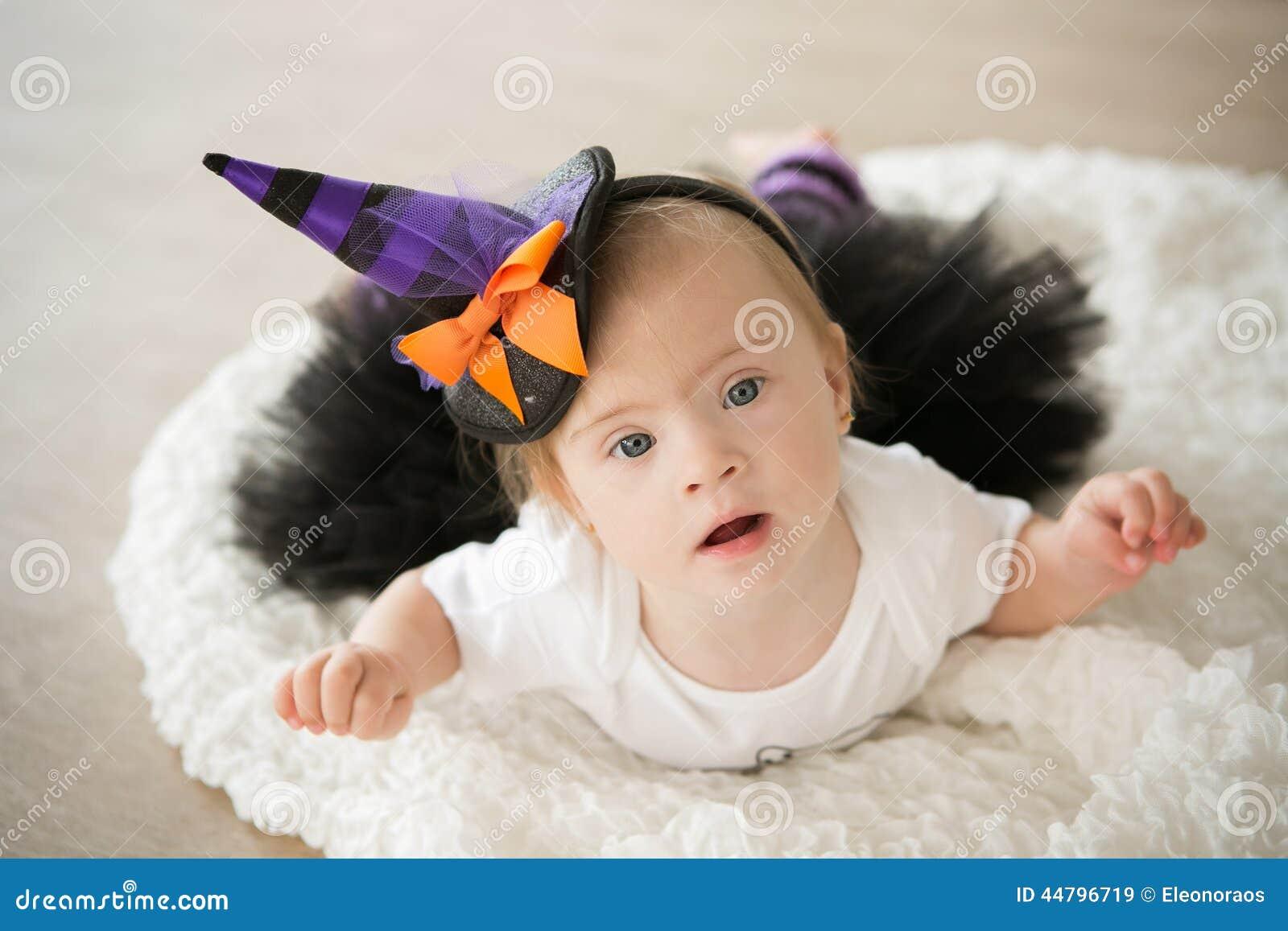 有唐氏综合症的美丽的小女孩在衣服一个小巫婆.图片