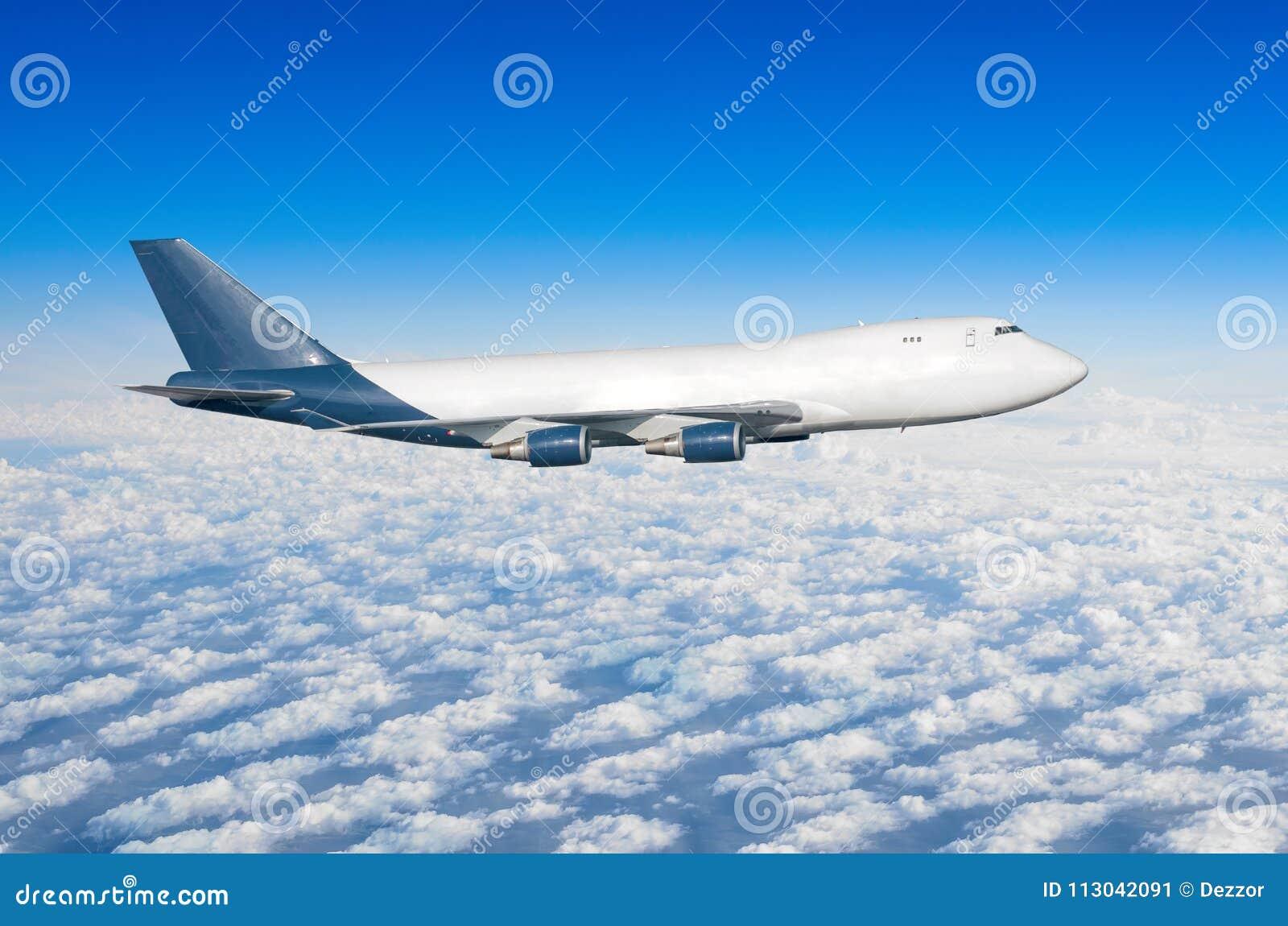 有四个引擎的飞机,没有舷窗的卡车在云彩飞行旅途太阳高度上的天空