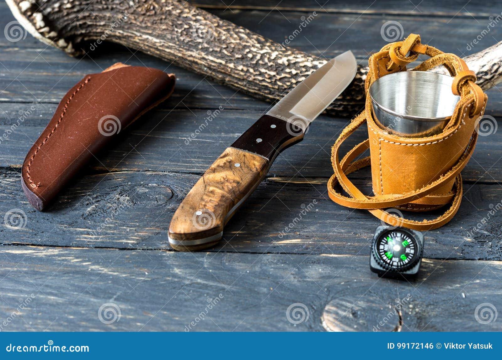 有固定的刀片和皮革鞘的刀子在鹿垫铁附近