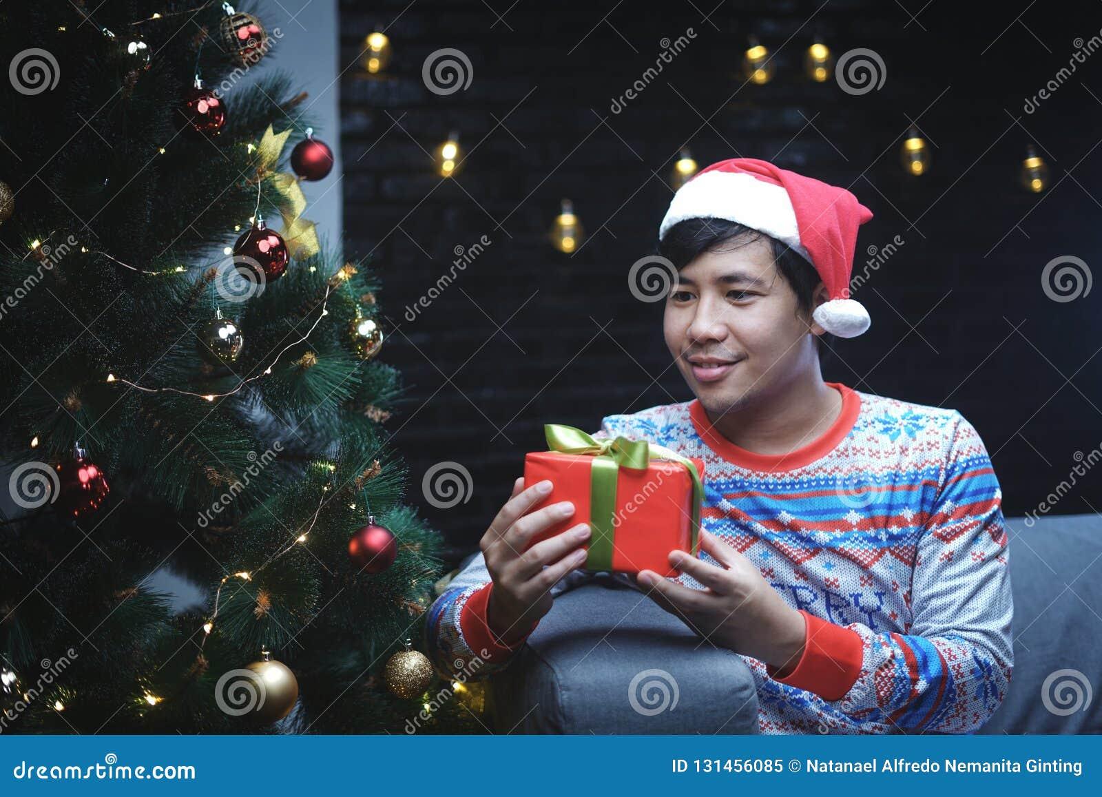 有圣诞节服装坐在圣诞树旁边的藏品圣诞礼物的亚裔人
