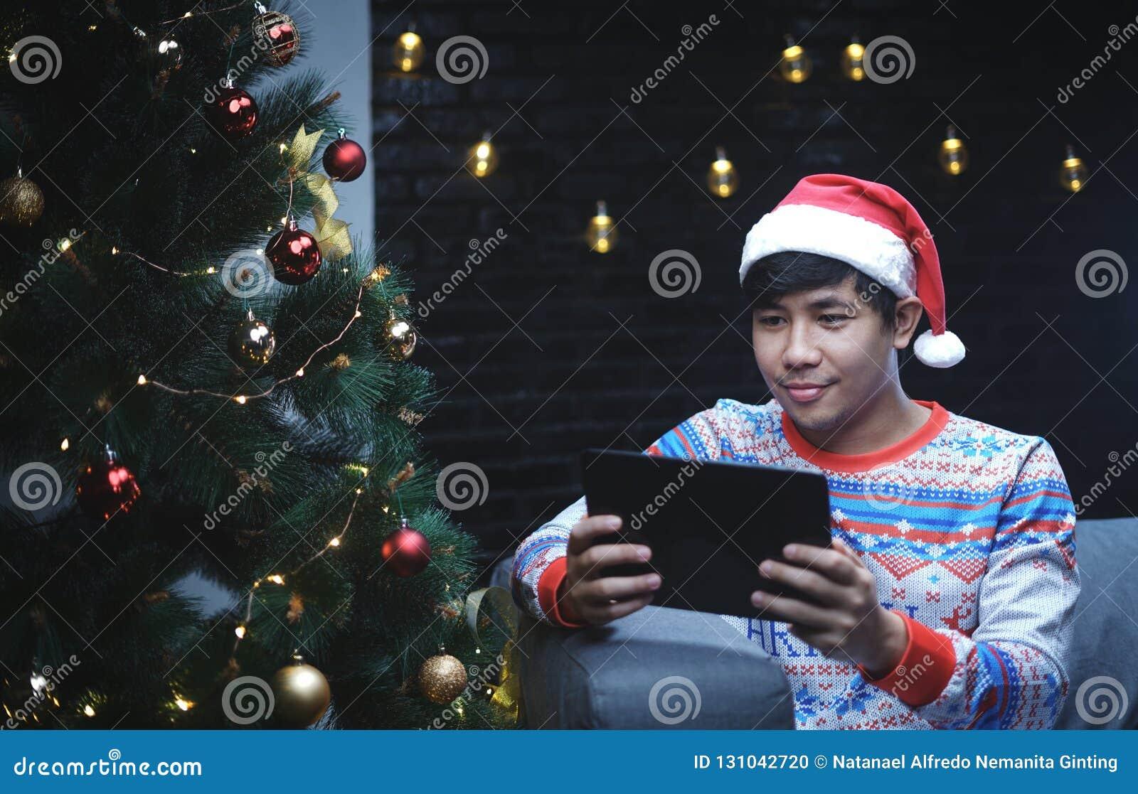 有圣诞节服装的亚裔人使用片剂设备,坐是