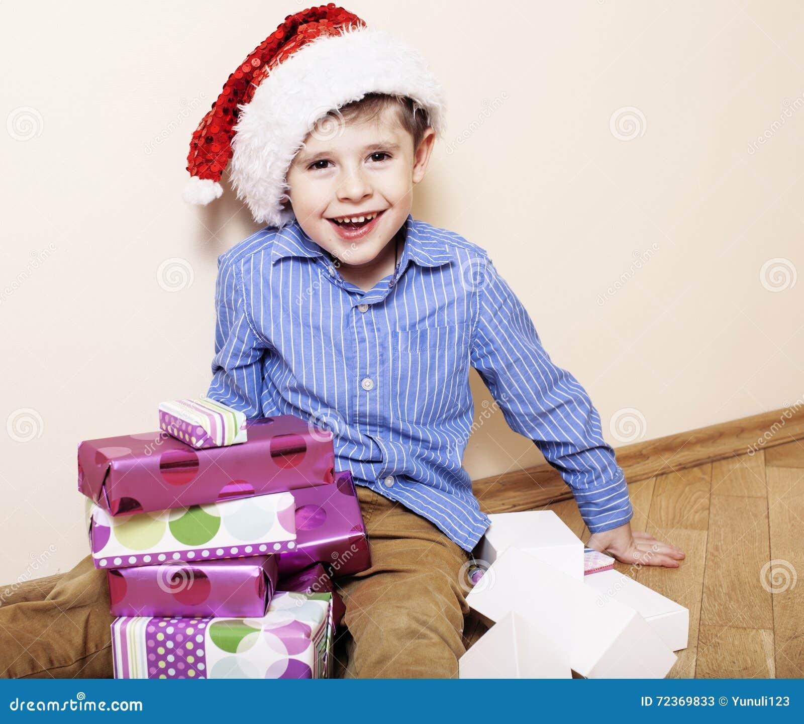 有圣诞节礼物的小逗人喜爱的男孩在家 关闭在箱子的情感面孔在圣诞老人红色帽子