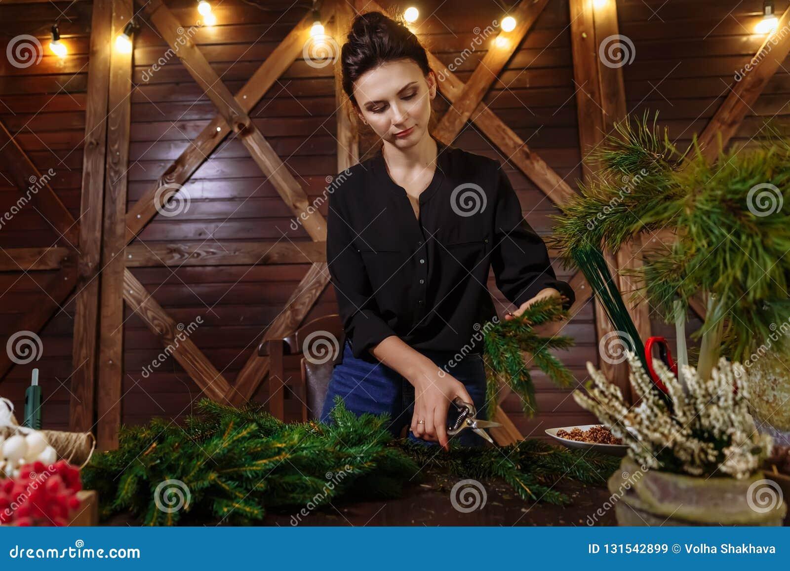 有圣诞节花圈的工作的卖花人妇女 准备圣诞节常青树花圈的年轻逗人喜爱的微笑的妇女设计师