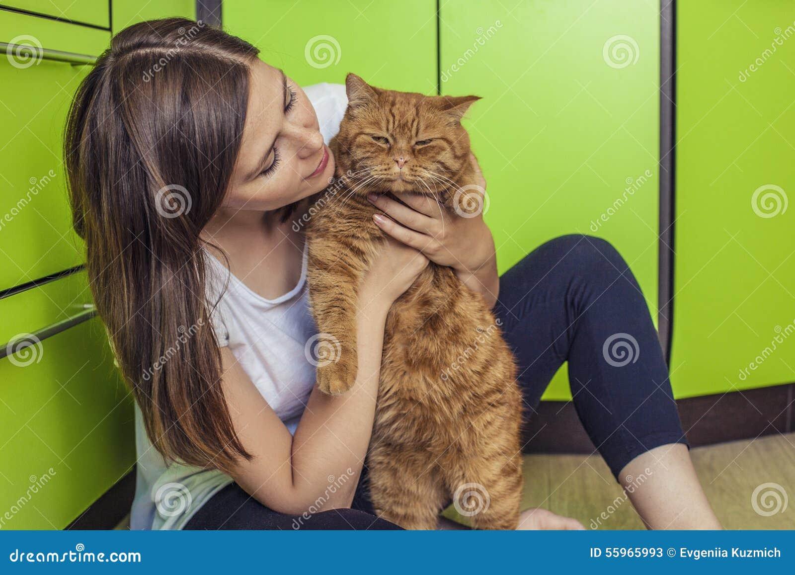 有在她的胳膊拥抱在厨房的一只姜猫的妇女