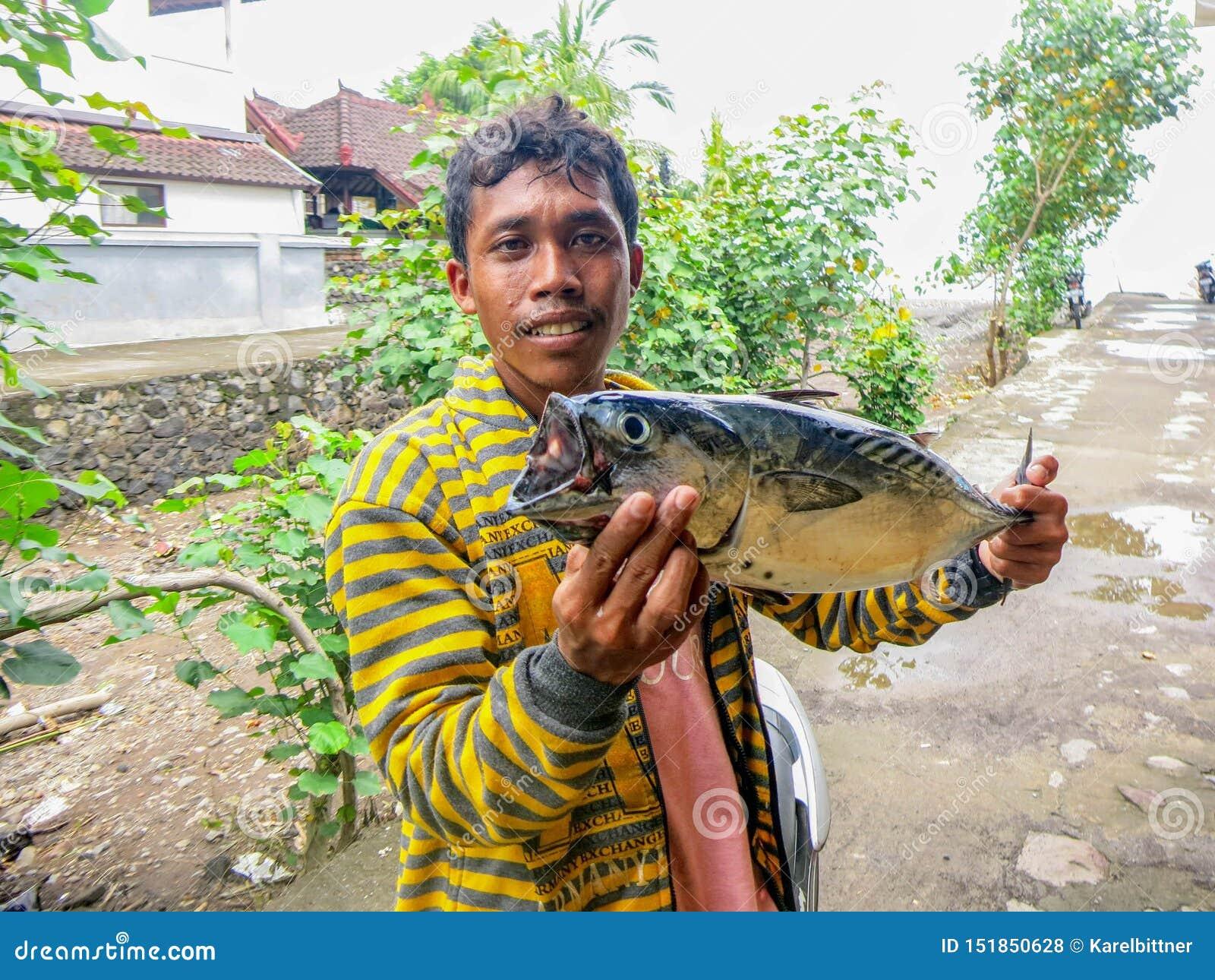 有在海捉住的金枪鱼的一位年轻渔夫 一位年轻印度尼西亚渔夫的一开心 鲜美鱼用精美肉 Sunn