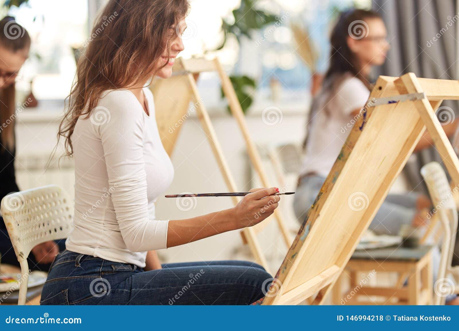 有在白色女衬衫穿戴的棕色卷发的微笑的女孩绘一幅画在画架在画的学校