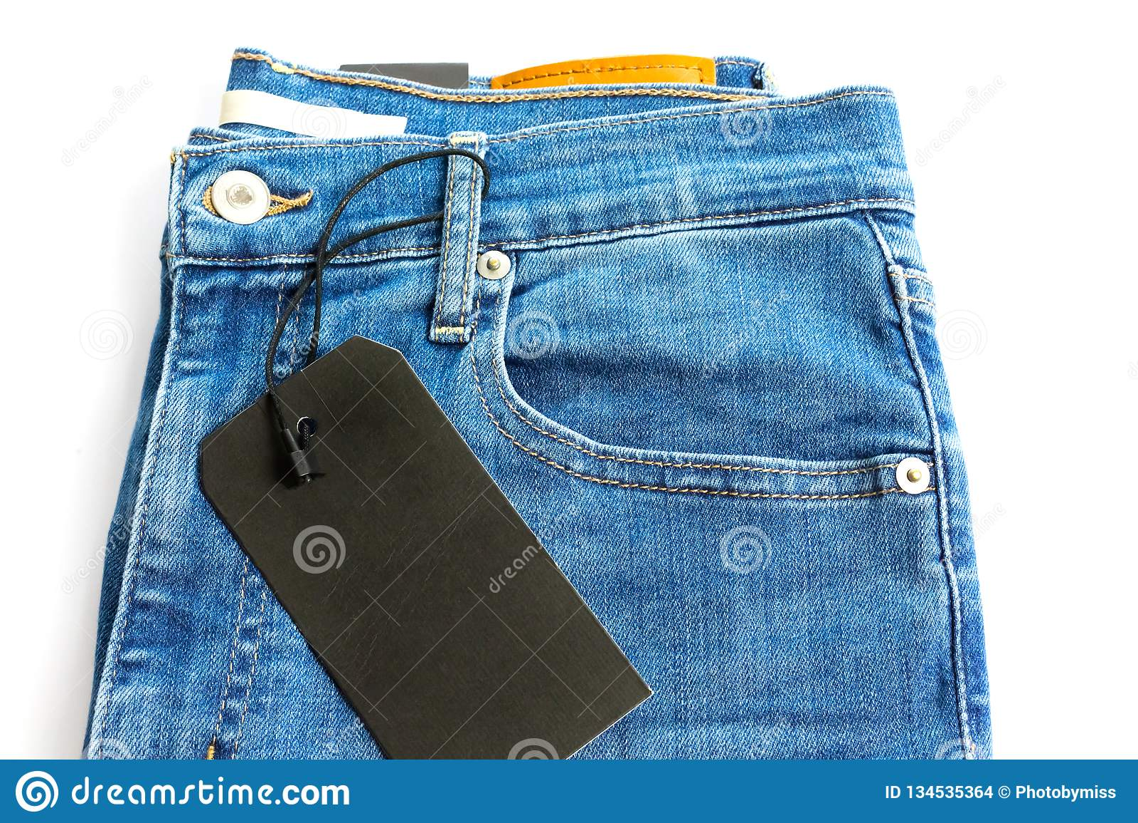 有在白色背景隔绝的空白的黑标签标记的蓝色牛仔裤
