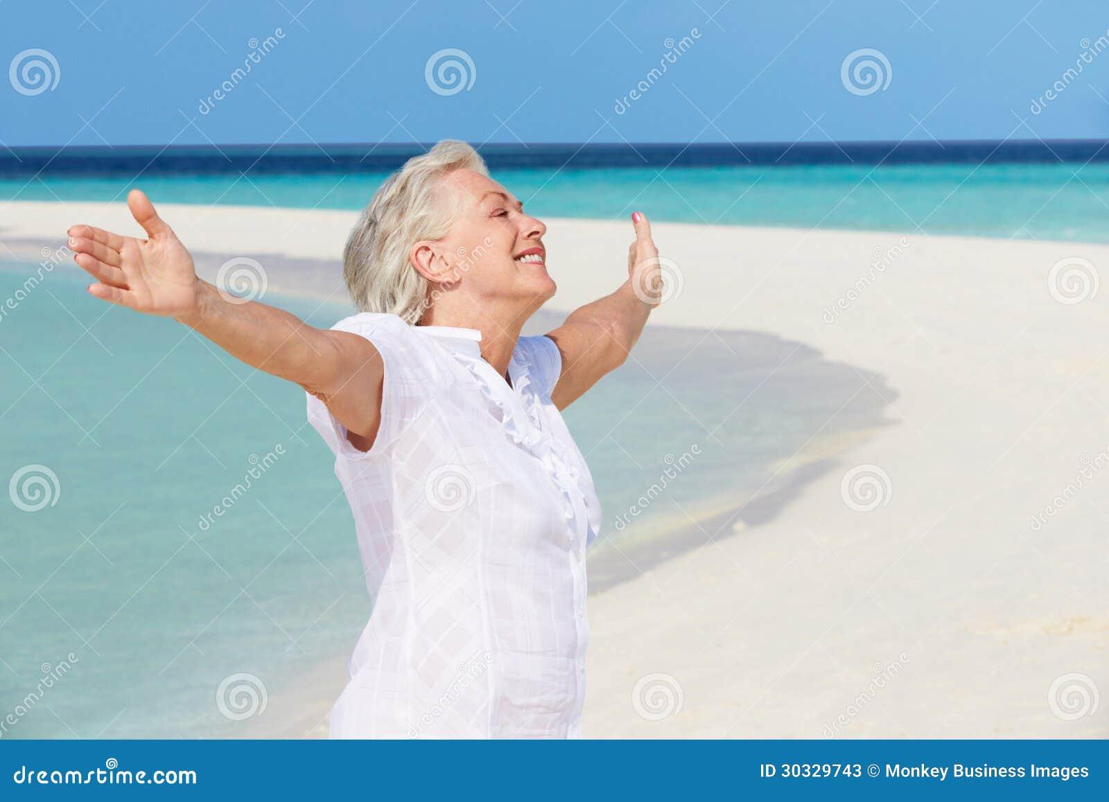 有在美丽的海滩伸出的胳膊的资深妇女