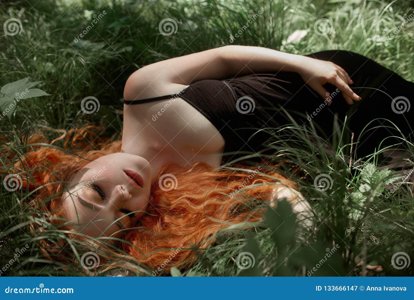有在草的红色头发的浪漫妇女在森林 一件轻的黑礼服睡眠和梦想的一个女孩在一个不可思议的森林里