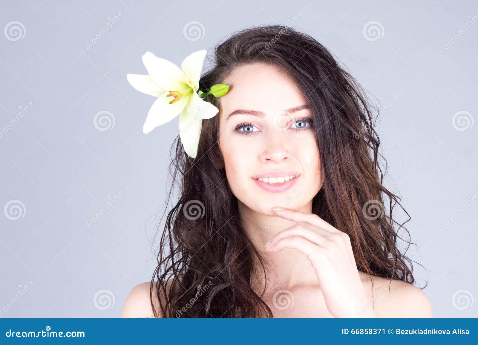有在头发微笑与牙和感人的下巴的卷发和百合的妇女 夏威夷心情