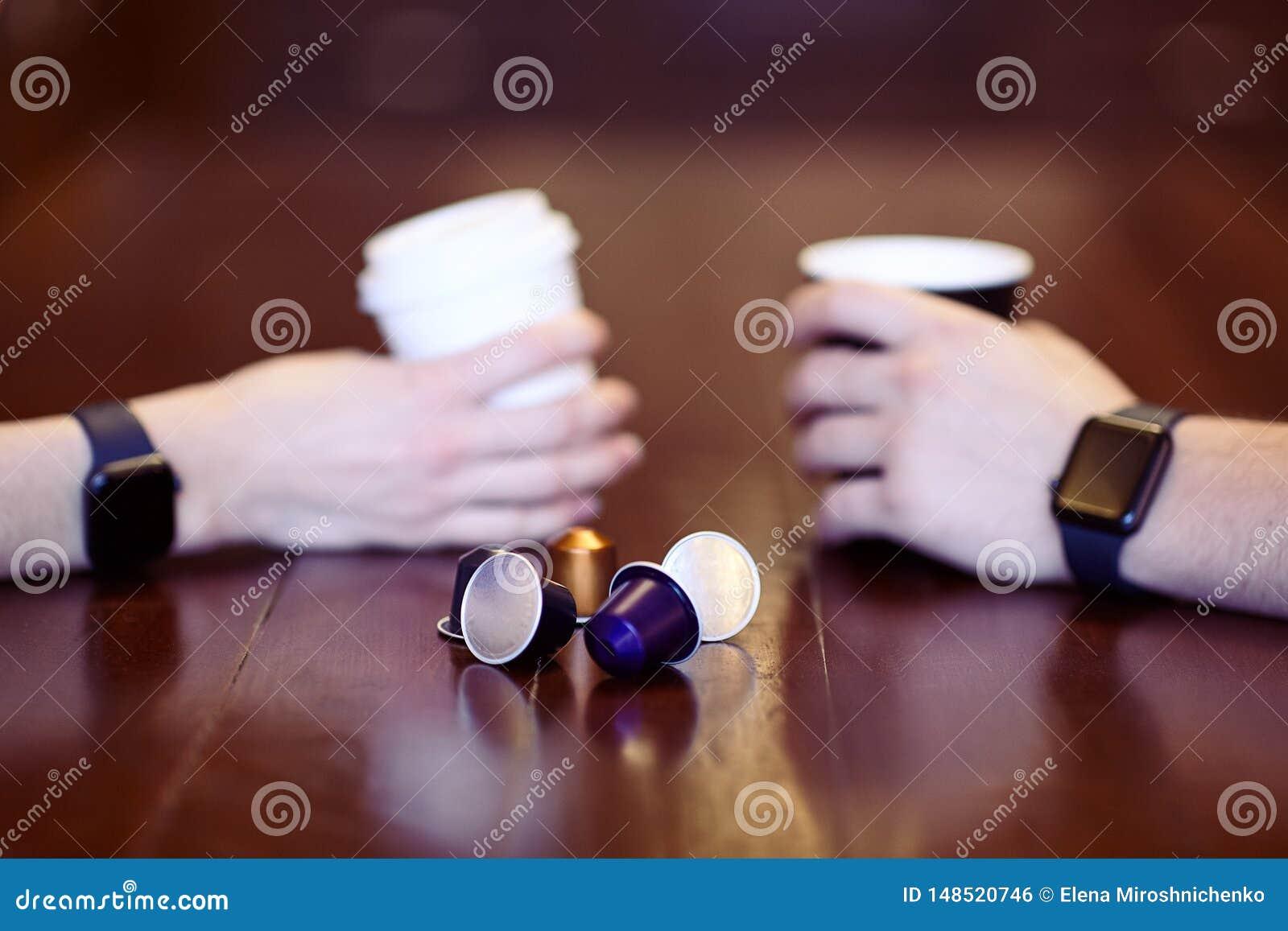 有均等黑色电子手表的两只手,拿着咖啡,白色和黑,在与一些replac的木桌上