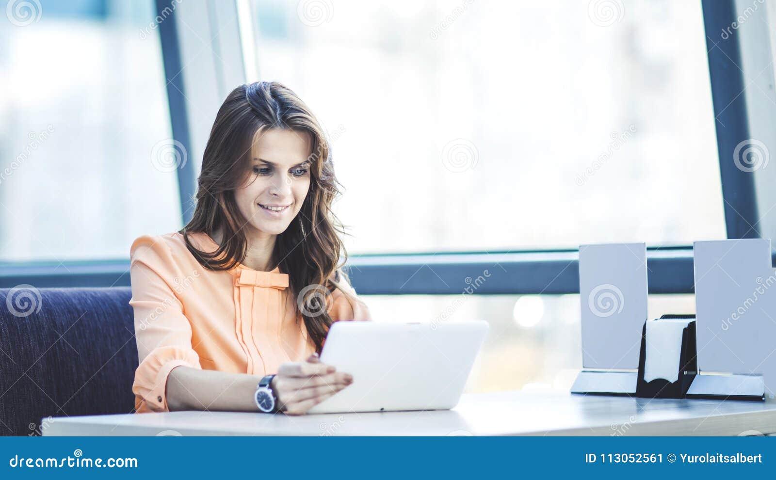 有坐在书桌的数字式片剂的成功的女商人在宽广的办公室
