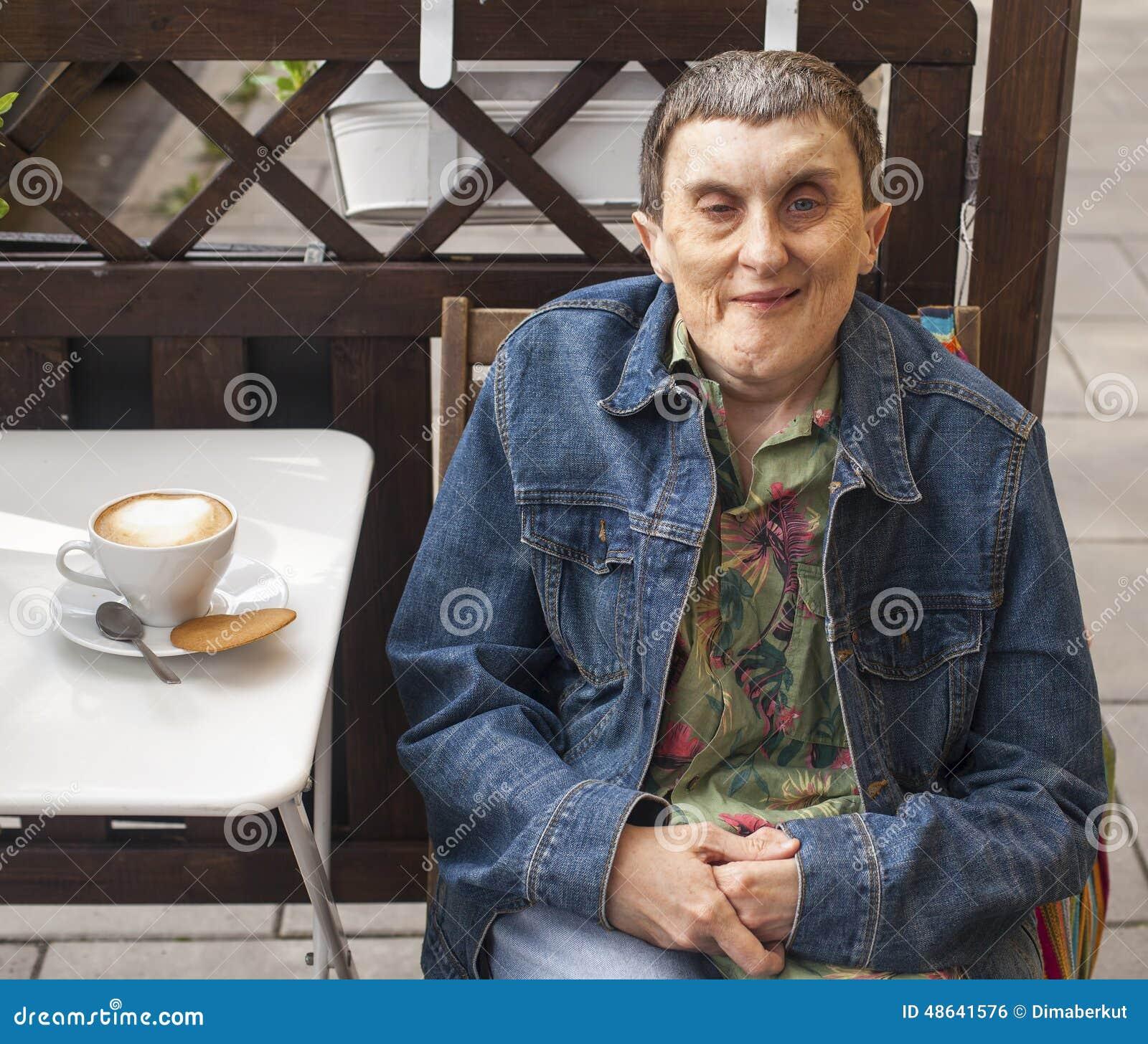 有坐在室外咖啡馆的大脑麻痹的残疾人