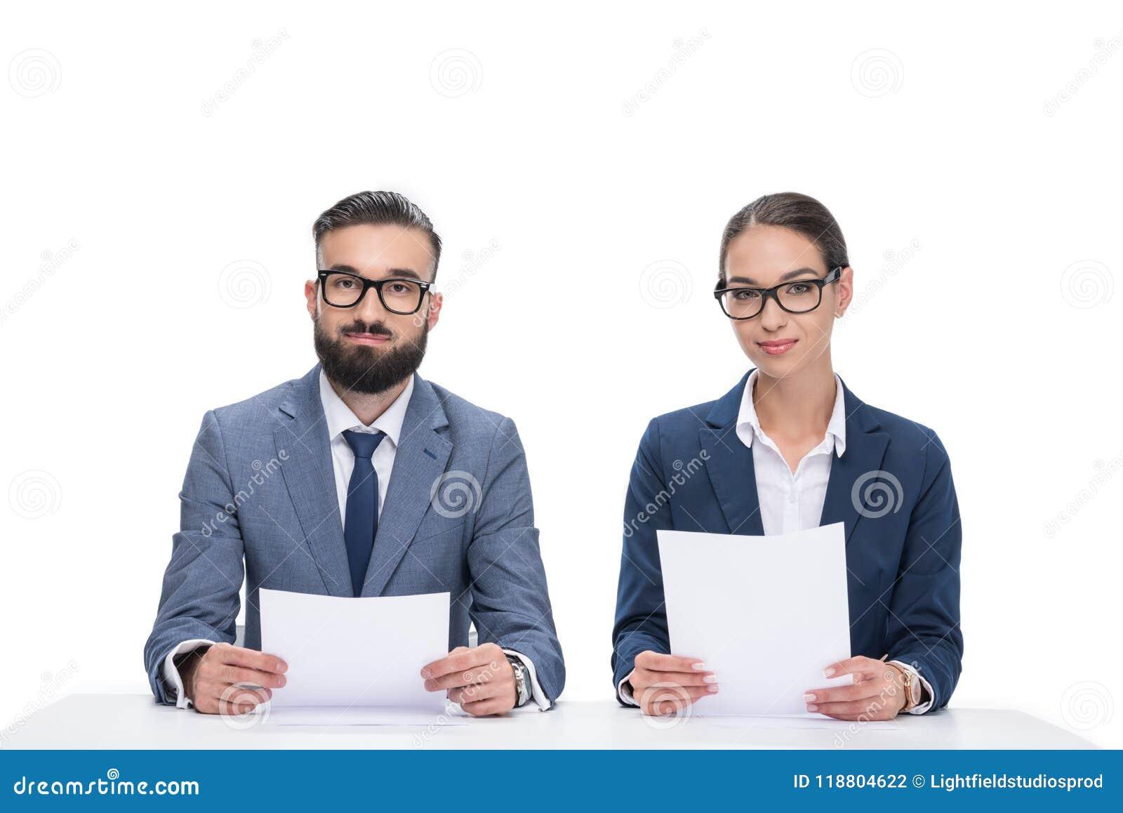 有坐在桌上和看照相机的纸的两个新闻广播员,