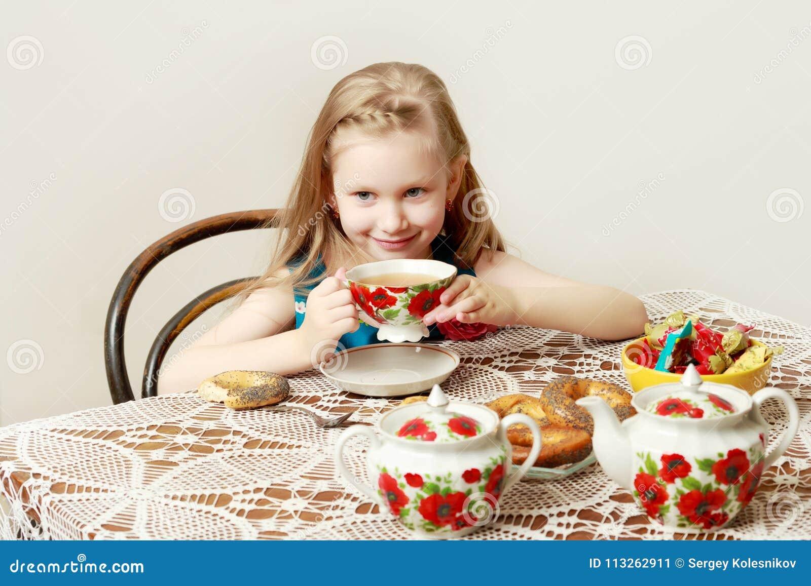 有坐在桌上的长的金发的一个美丽的小女孩
