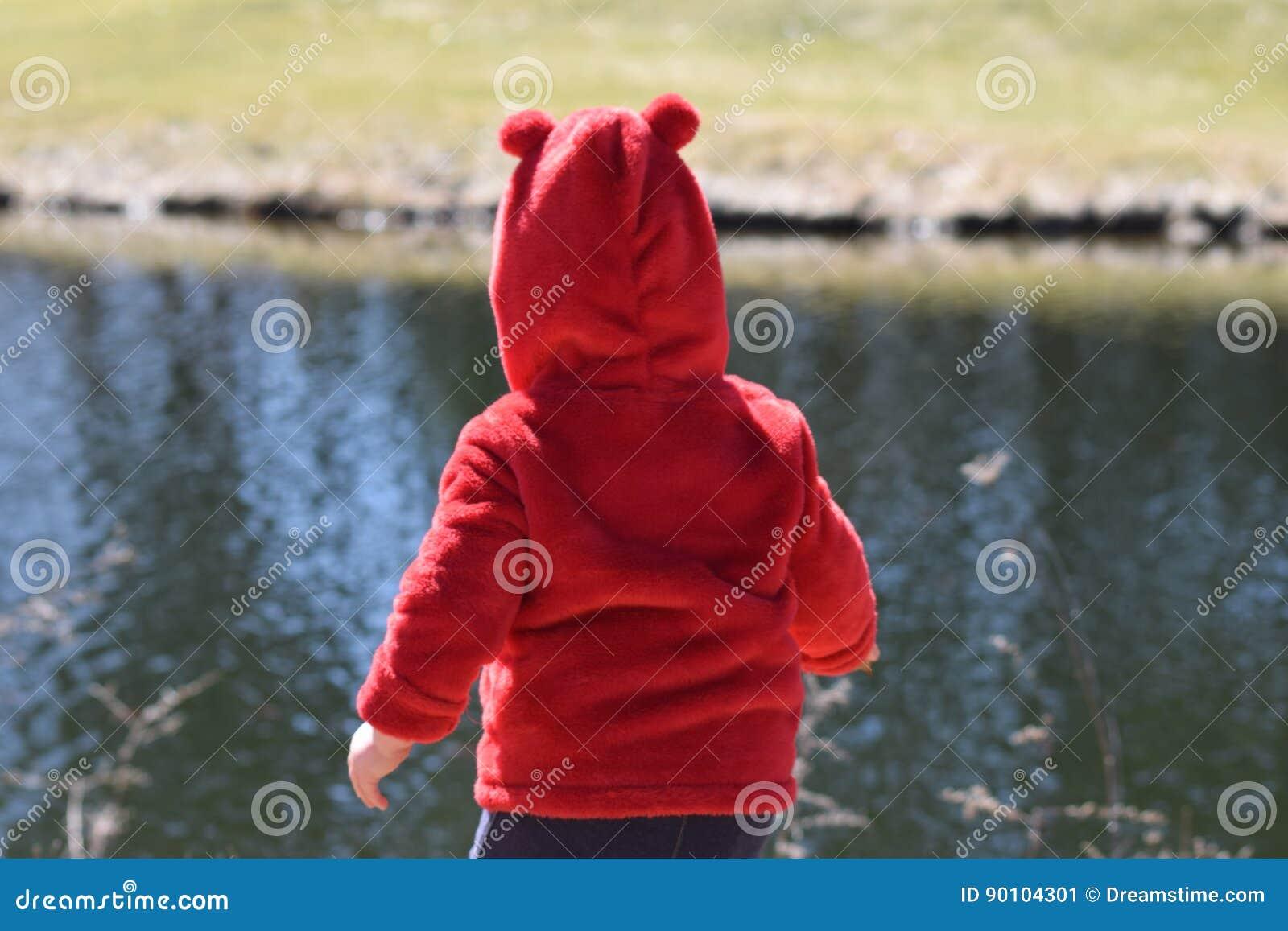 有坐在池塘前面的红色外套的小孩