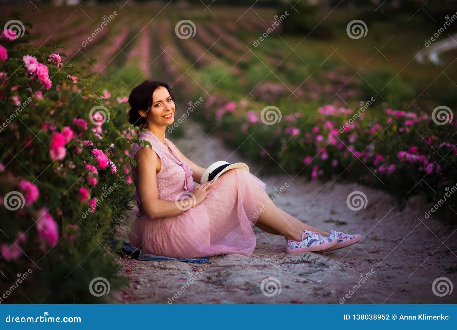 有坐在玫瑰的黑发的美丽的年轻女人调遣 芳香、化妆用品和香水广告