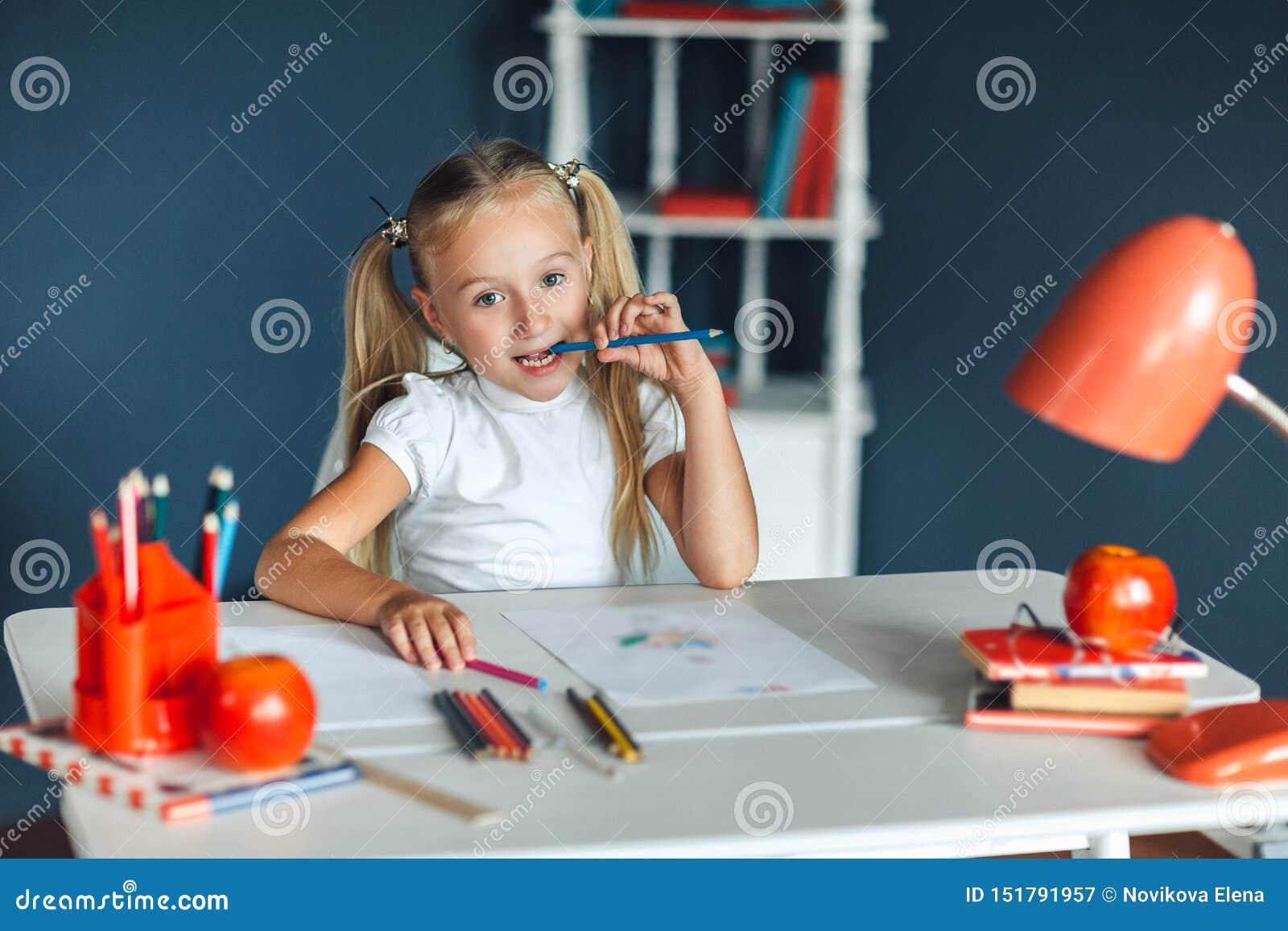 有坐在白色桌上和拿着在她的嘴的金发的滑稽的女孩紫色铅笔