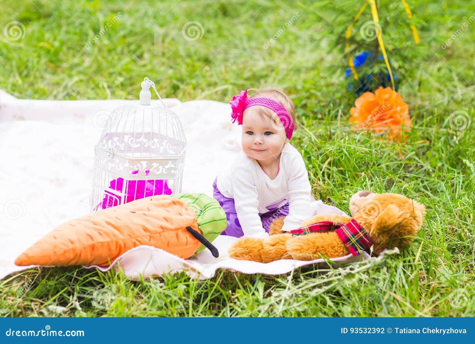 有大棕色女用连杉衬裤的逗人喜爱的矮小的愉快的女婴涉及绿草草甸、春天或者夏季