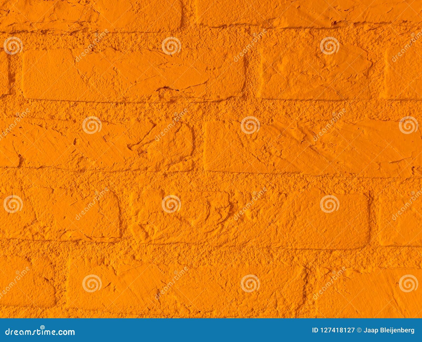 有大砖的现代充满活力的橙色石砖墙接近背景样式