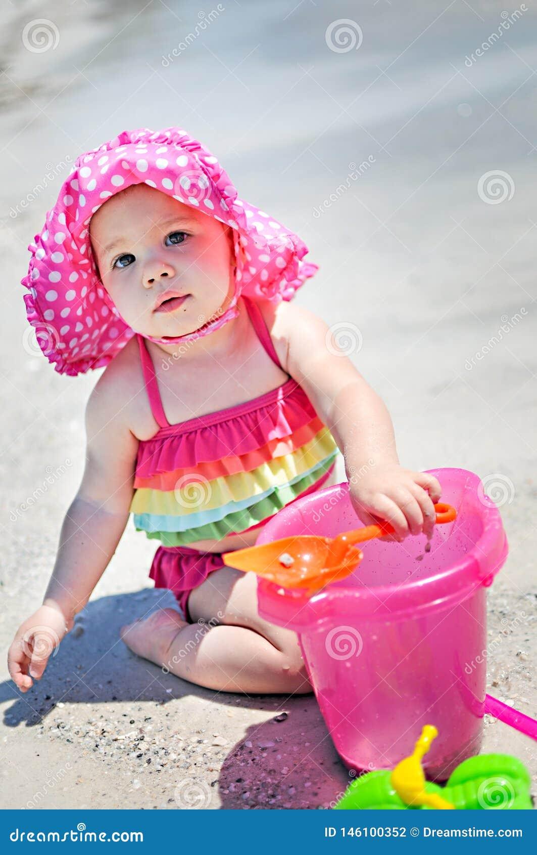 有太阳帽子的女婴在使用在海滩的沙子