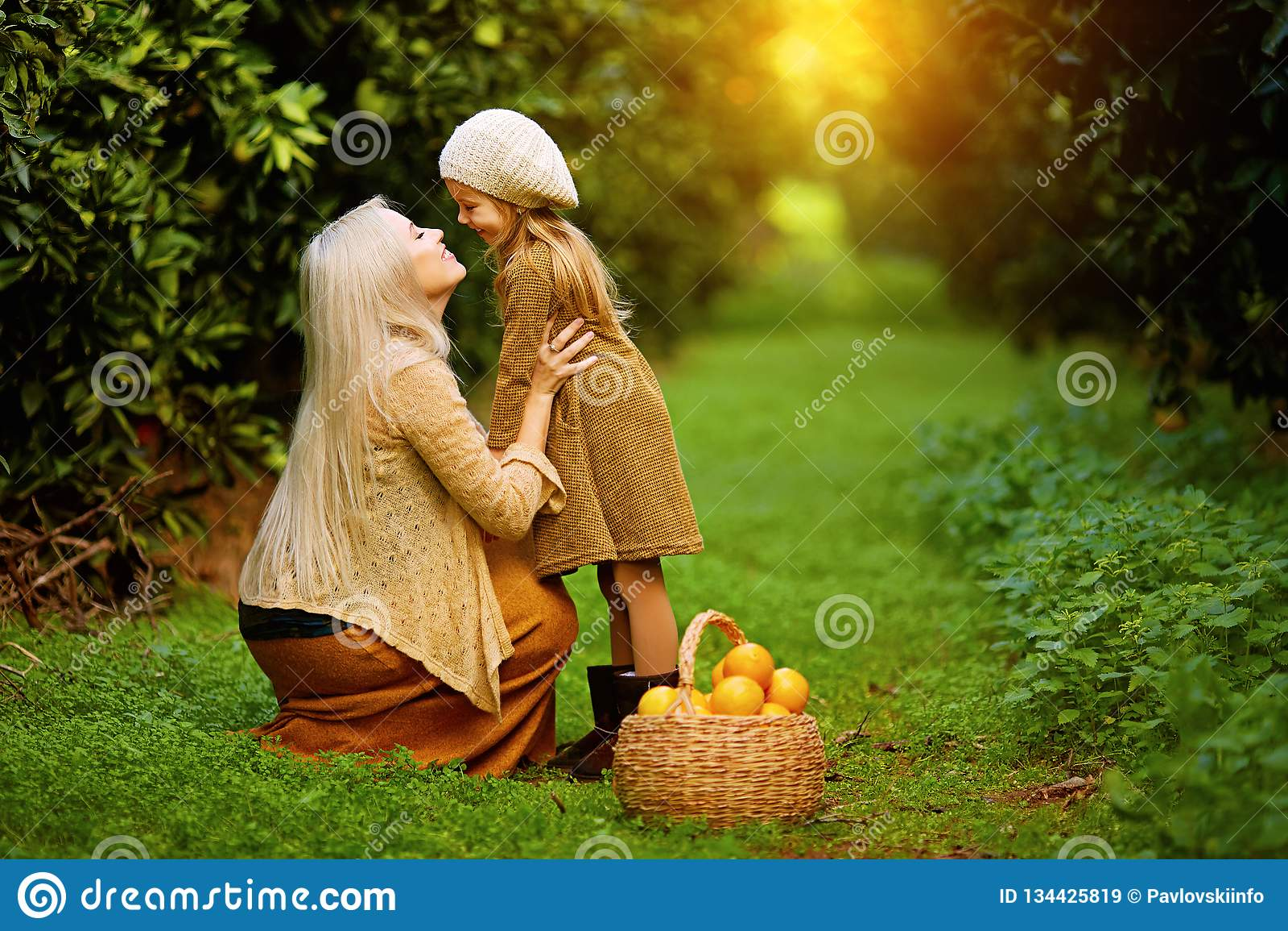 有女儿的愉快的妇女在晴朗的庭院里