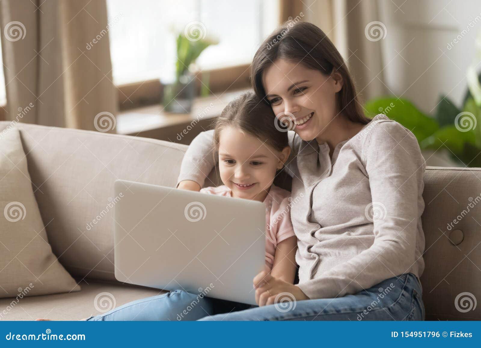 有女儿的母亲坐在膝上型计算机的长沙发电影