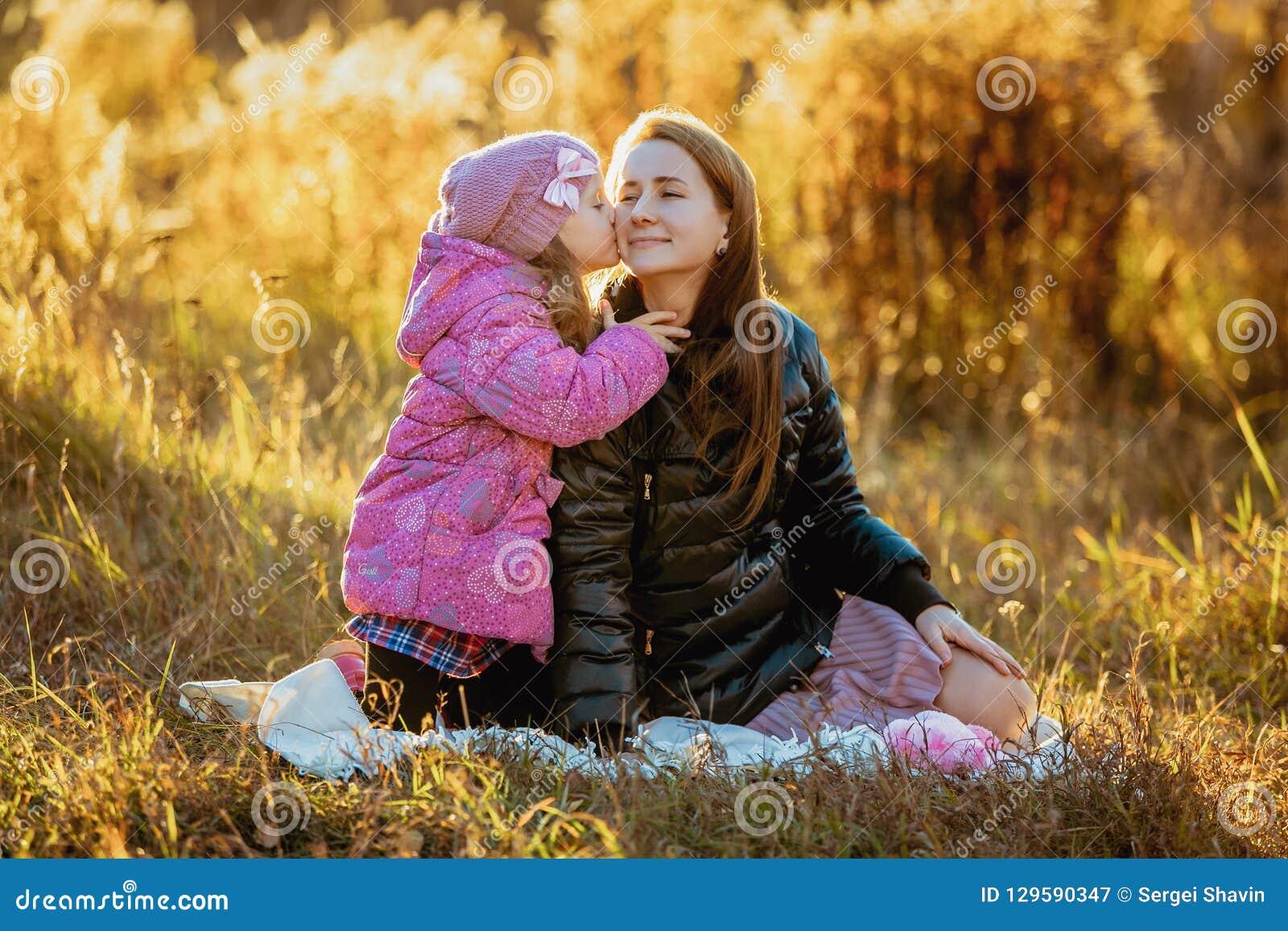 有她的女儿的年轻美丽的母亲步行的在一晴朗的秋天天 他们坐在草,女儿kisse的格子花呢披肩