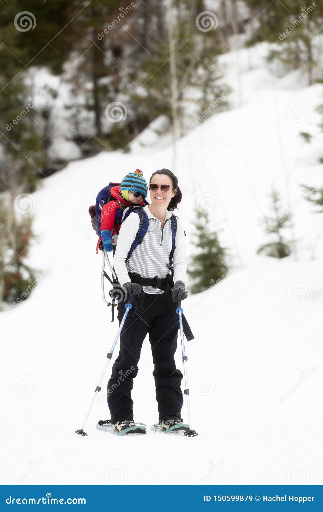 有她的婴孩的年轻妈妈Snowshoeing背包的