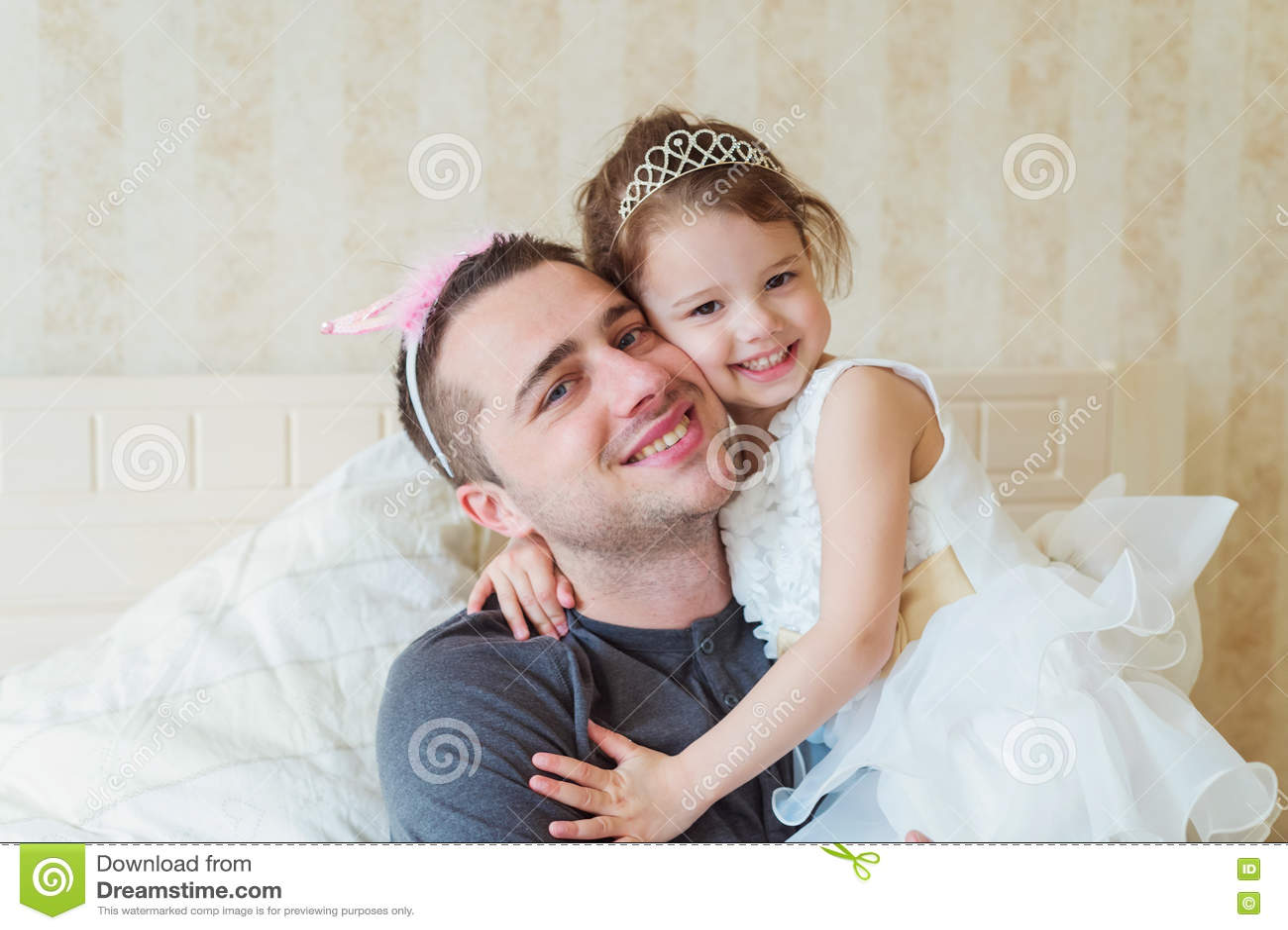 有她的父亲佩带的冠的逗人喜爱的小女孩