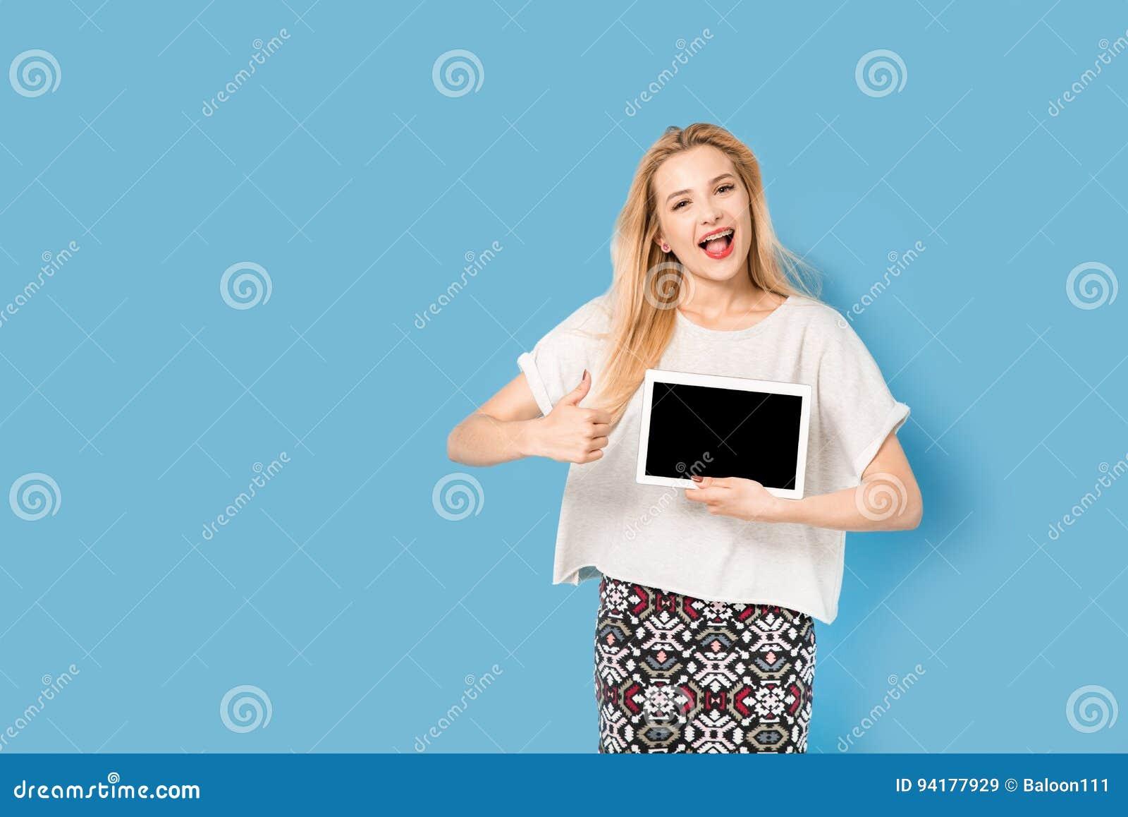 有她的片剂个人计算机的年轻美丽的女孩显示