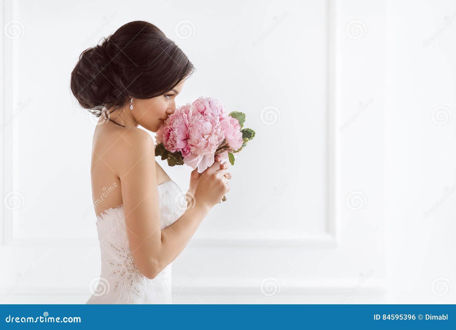 有她的花的美丽的新娘 婚礼发型构成豪华时尚礼服和花束