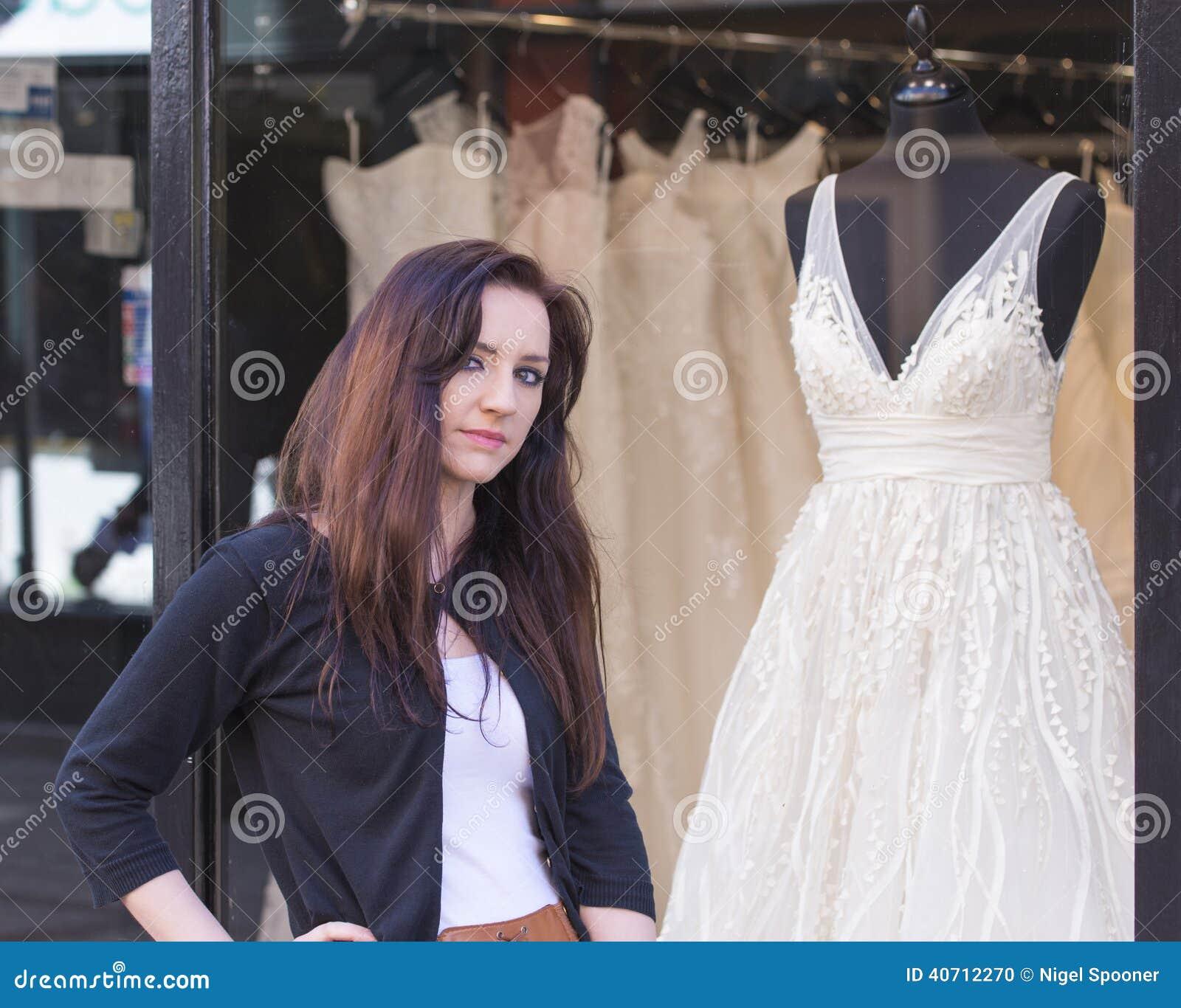 有婚礼礼服商店窗口的妇女