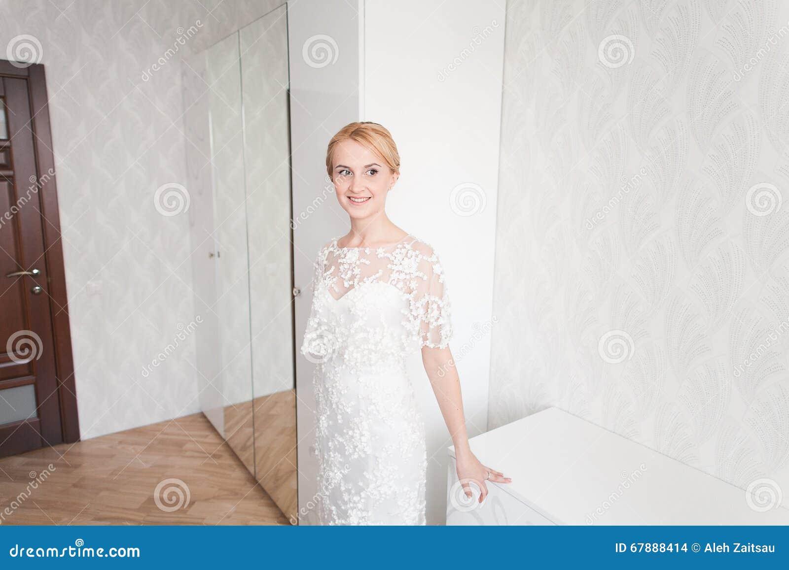 有婚礼花束构成和发型的华美的新娘在家等待新郎的新娘礼服