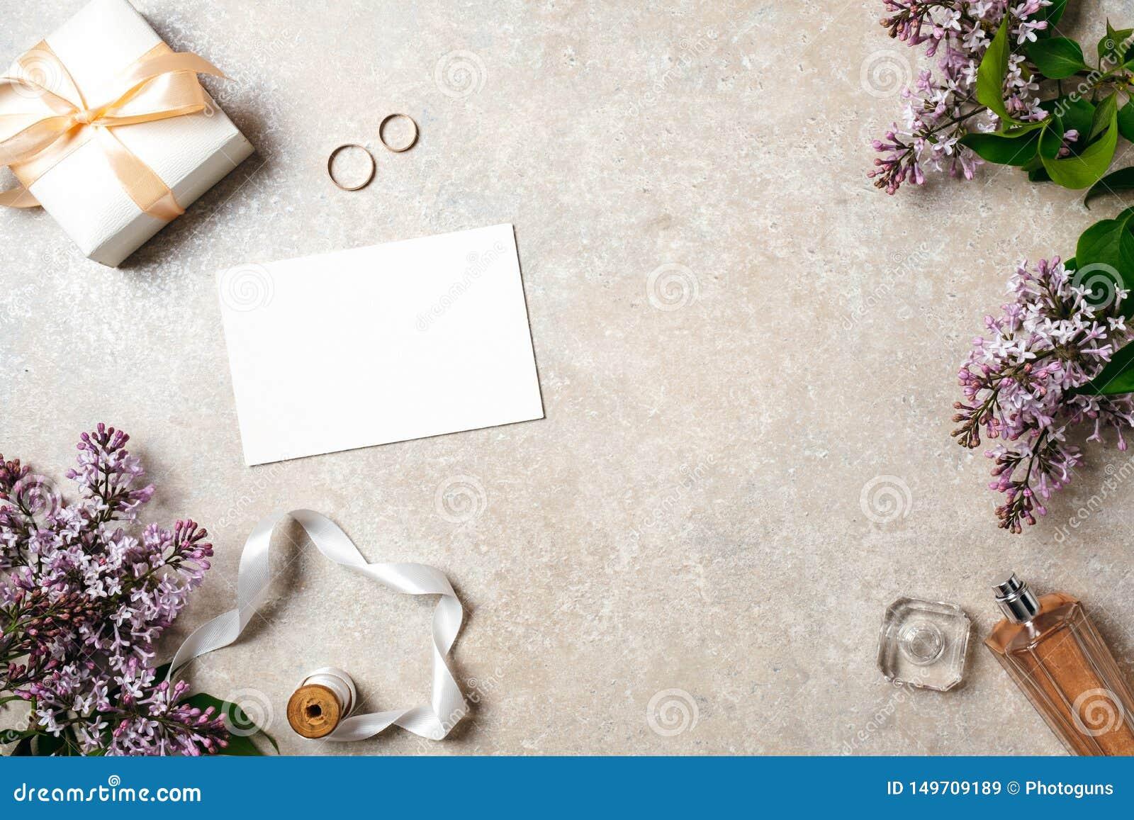 有婚礼辅助部件、白纸卡片、圆环和春天淡紫色花的女性书桌 婚礼概念,请帖嘲笑