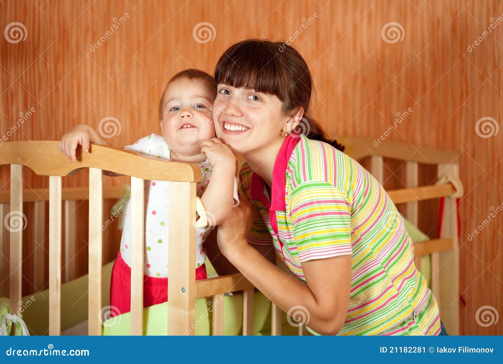 有婴孩的愉快的母亲小儿床的