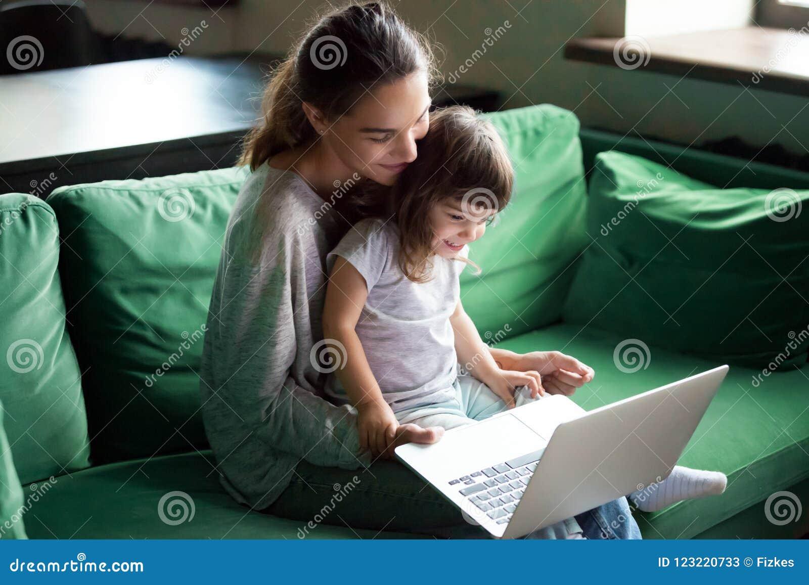 有孩子女儿的愉快的母亲获得乐趣在网上与膝上型计算机