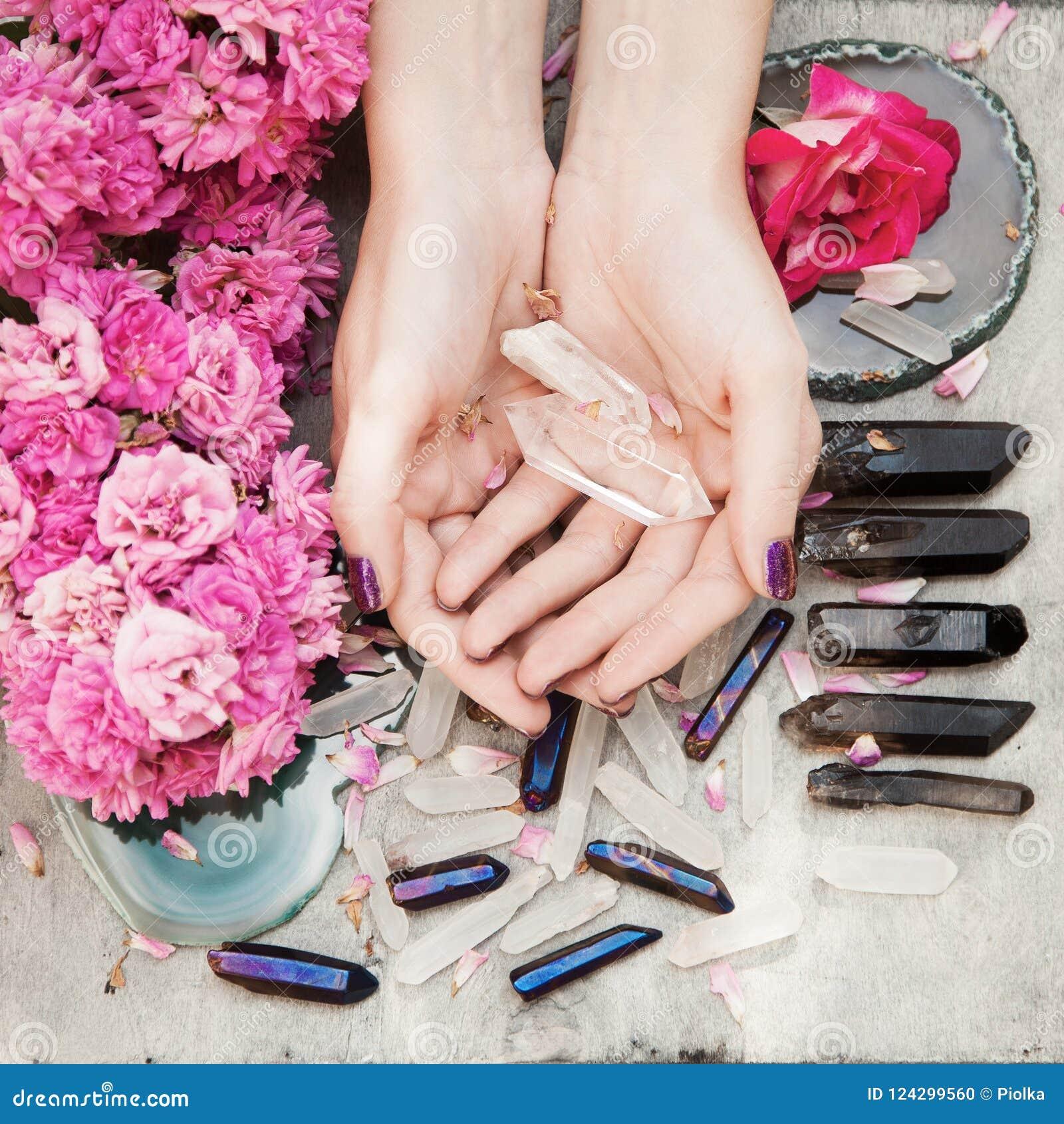 有完善的紫罗兰色的美好的妇女手在拿着一点水晶的白色木背景指甲油