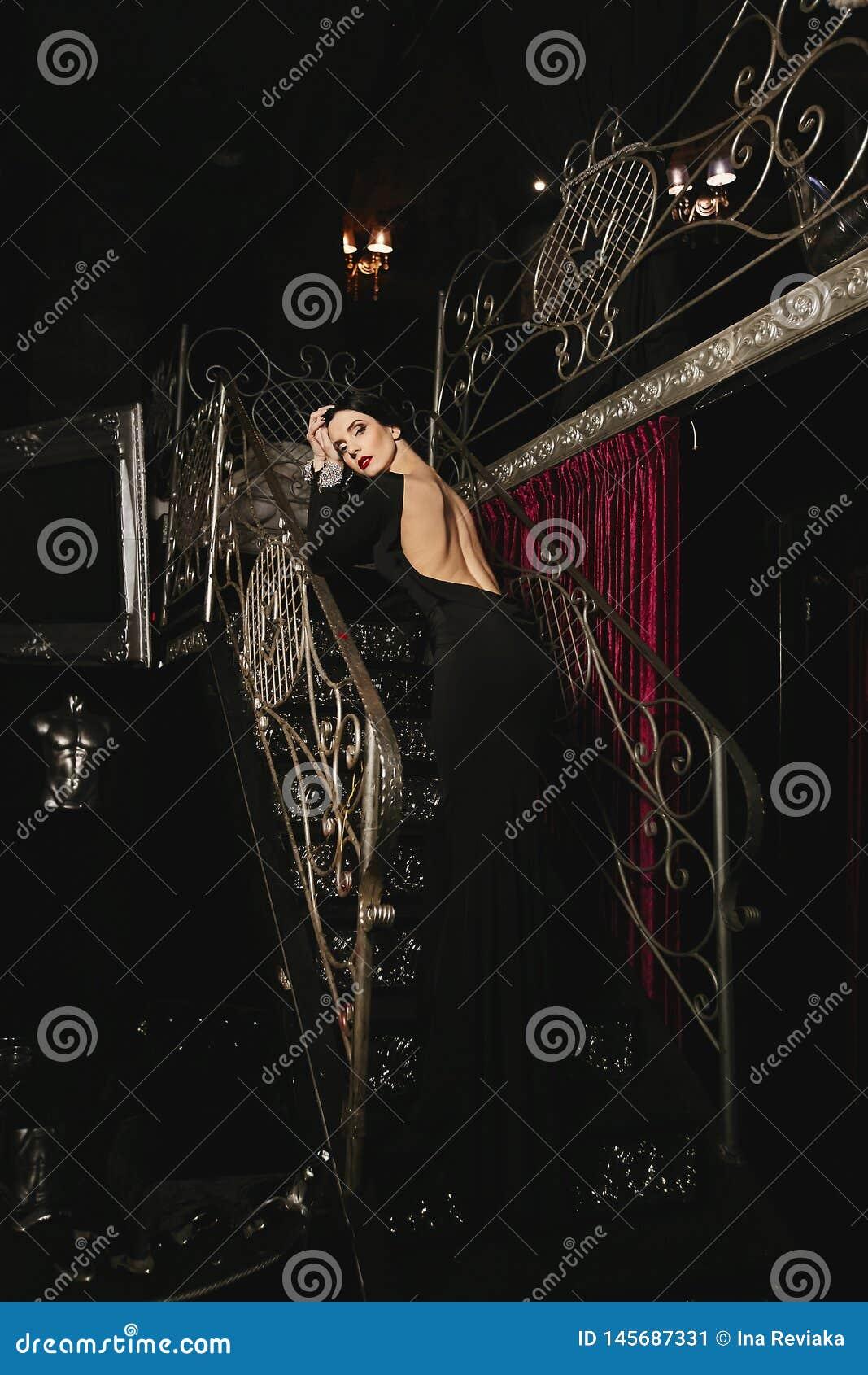 有完善的身体的时兴和性感的深色的式样女孩和在黑晚礼服的红色嘴唇与摆在的裸体后面
