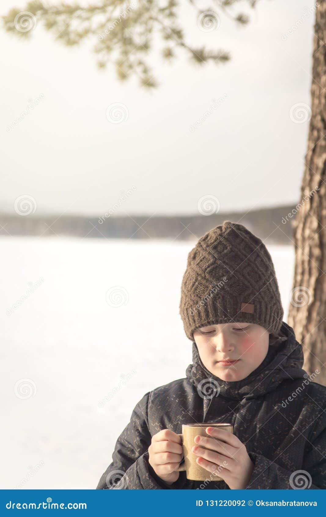 有室外热的冬天的饮料的男孩