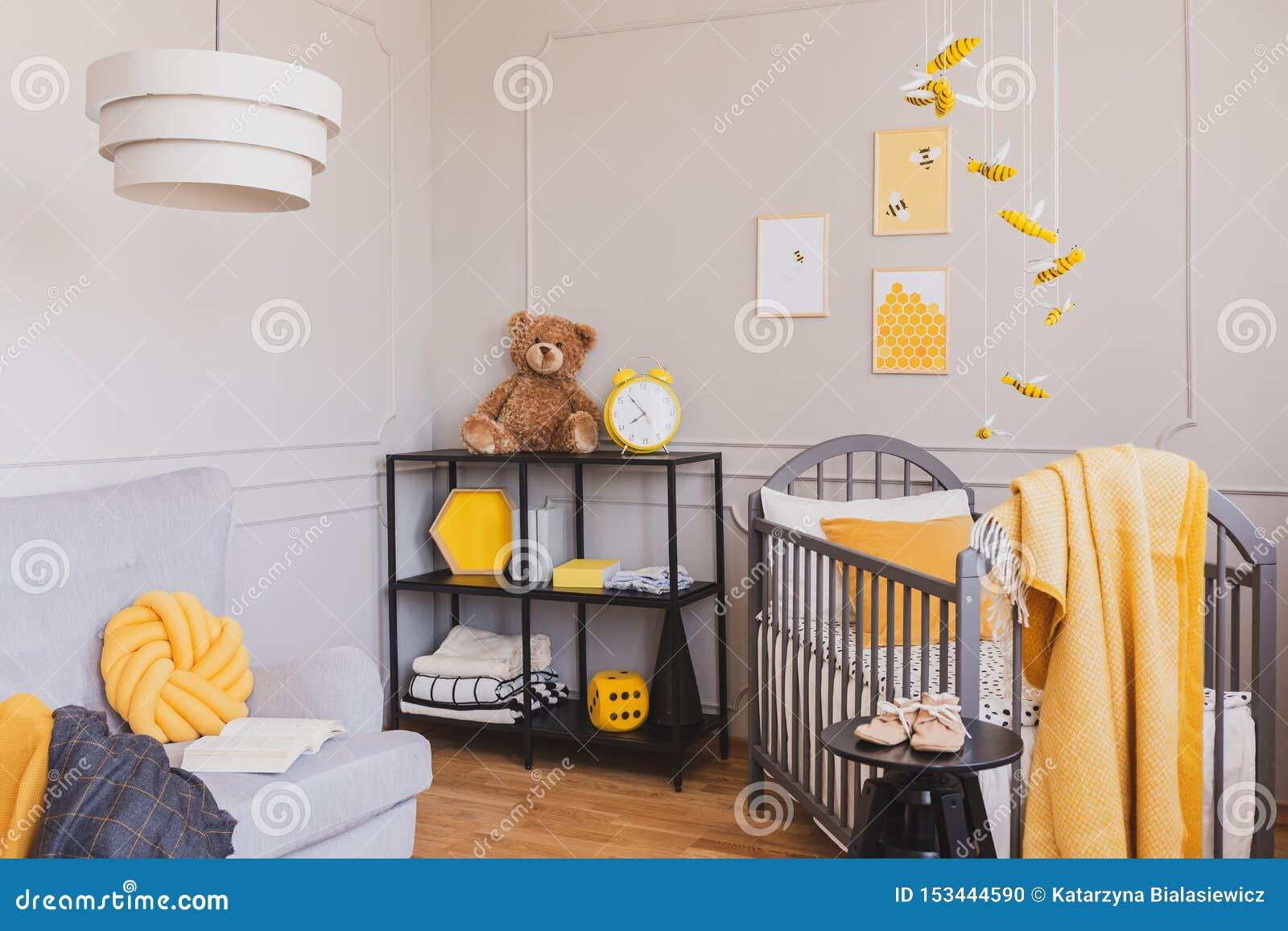 有小儿床和工业黑金属架子的时髦的灰色和黄色婴孩卧室