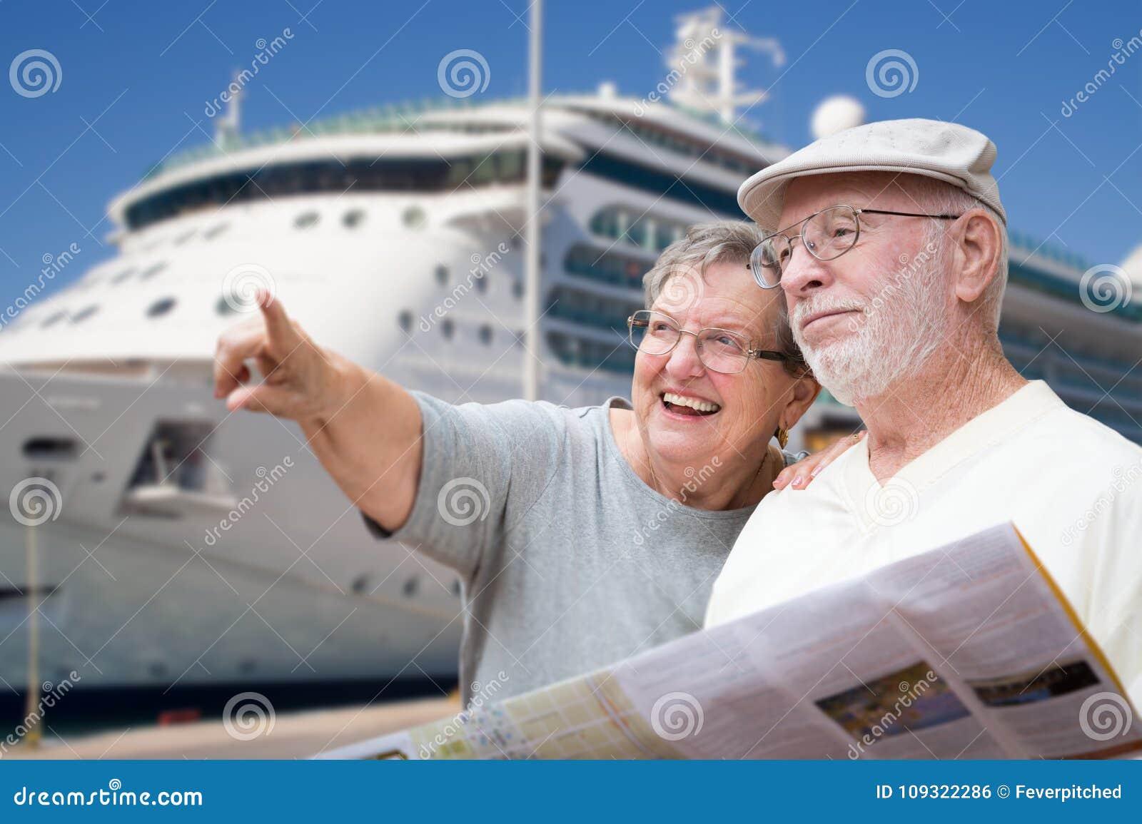 有小册子的愉快的资深成人夫妇游人由游轮