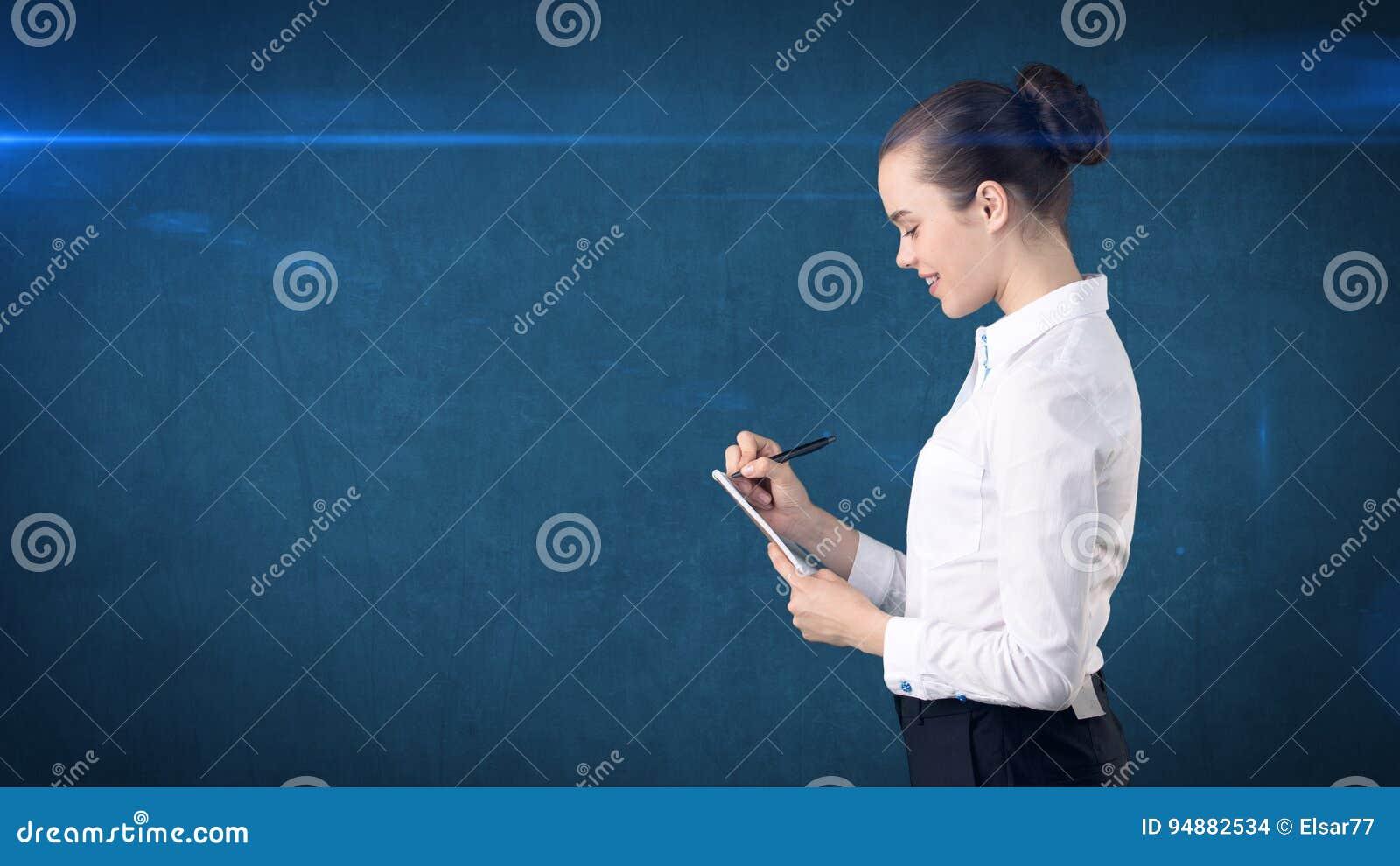 有小圆面包文字的专业确信的女实业家在演播室背景隔绝的她的组织者 到达天空的企业概念金黄回归键所有权